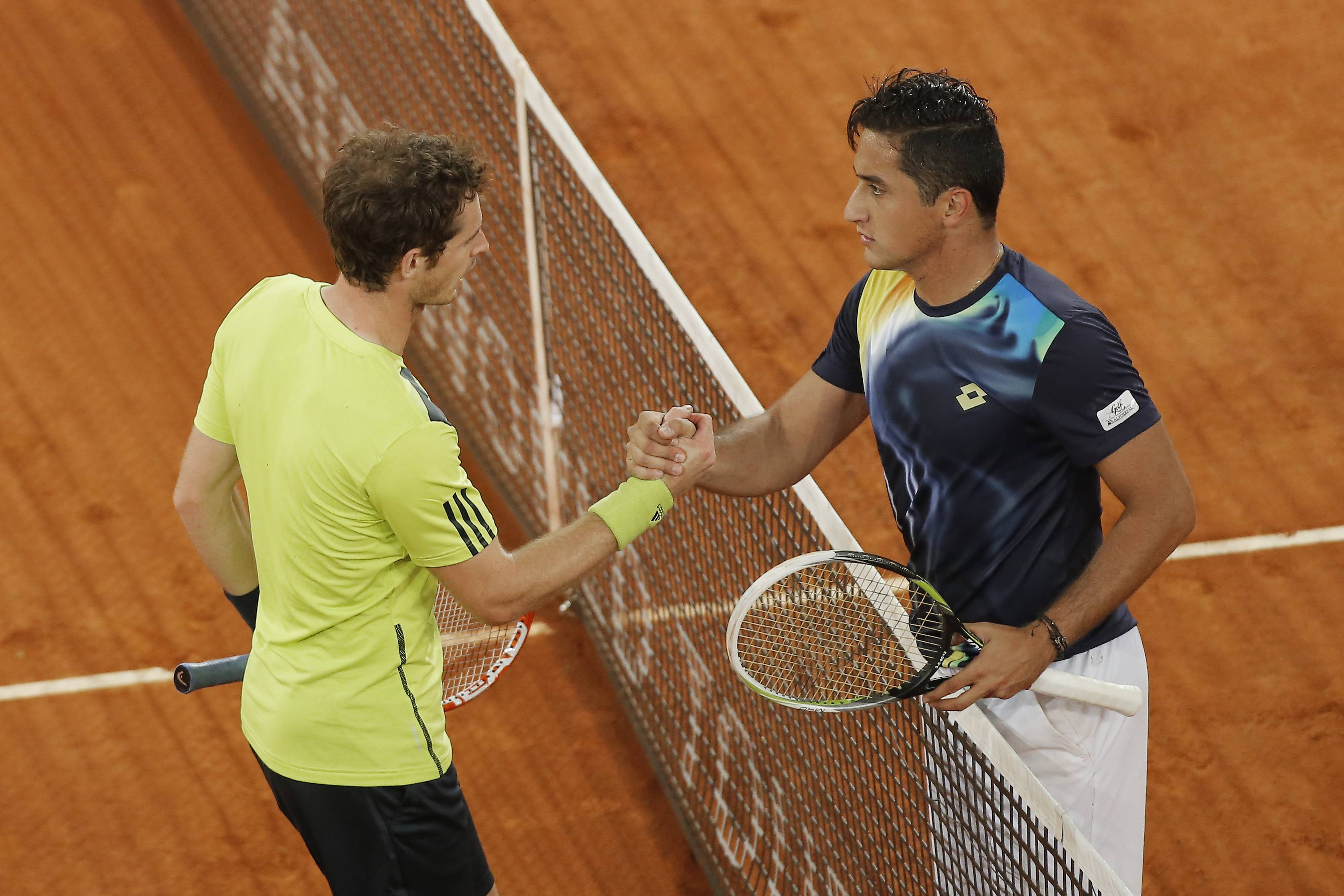 Nicolas Almagro from Spain, right, shakes hands with Britain's Andy Murray, left, after a Madrid Open tennis tournament match in Madrid, Spain, Wednesday, May 7, 2014.