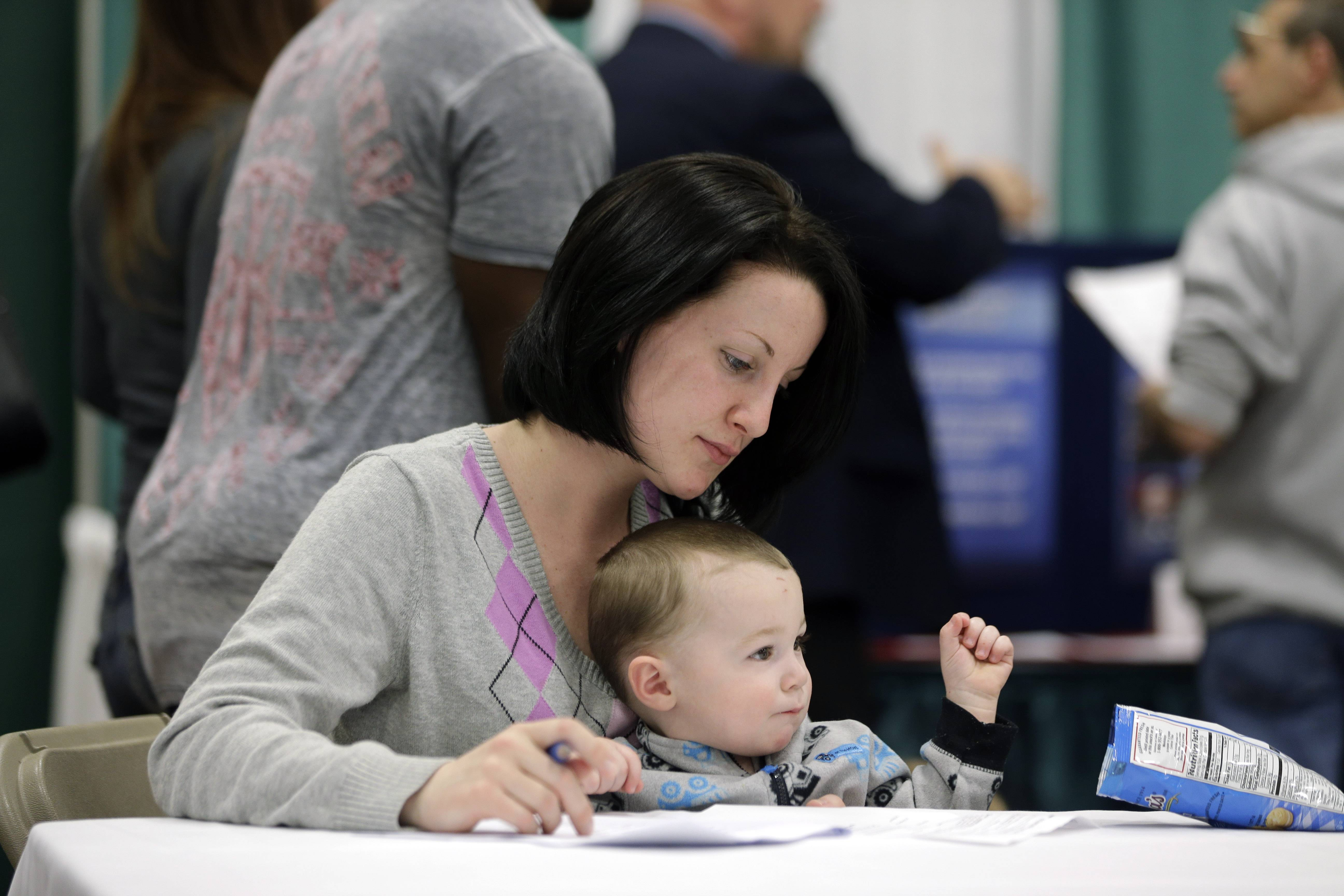 Sarah Keegan of Windham, N.Y., with her son Kevin, fills out paperwork during a job fair at Columbia-Greene Community College in Hudson, N.Y.
