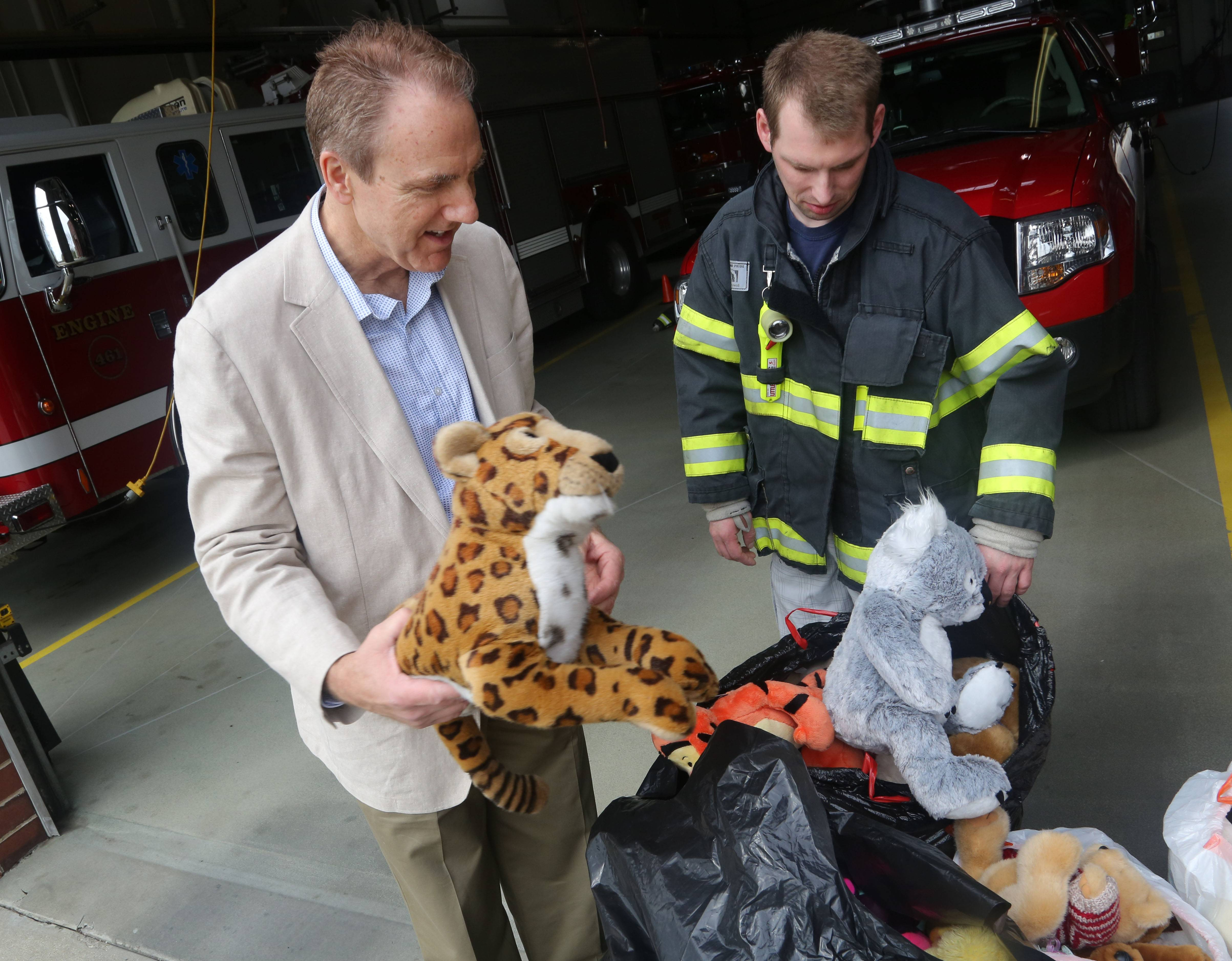 Libertyville chiropractor Dr. Tom Bennett, left, and Libertyville firefighter Brian Bagdon look through bags of stuffed animals Bennett collected from patients and donated at the Libertyville fire station headquarters Thursday. The animals are given to kids on emergency calls.