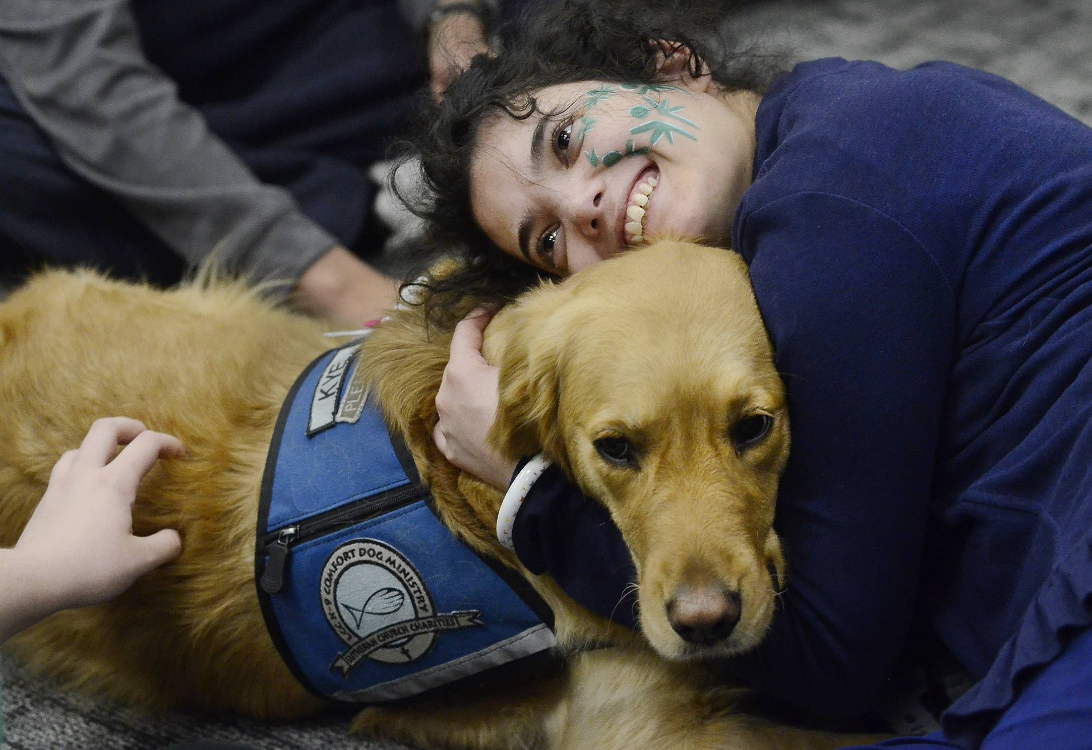 Katie Livingston hugs Kye, one of the Comfort Dogs on the campus of Harper College to help de-stress students Wednesday before finals.