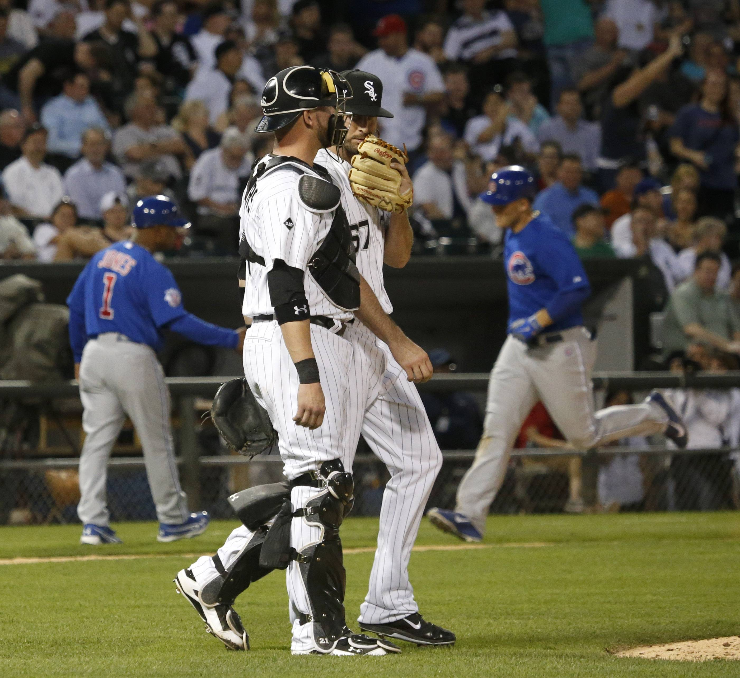 Chicago White Sox starting pitcher Scott Carroll (67) walks back to the mound with catcher Tyler Flowers after giving up a two-run home run to Chicago Cubs' Anthony Rizzo, background right, during the third inning of an interleague baseball game Thursday, May 8, 2014, in Chicago. (AP Photo/Charles Rex Arbogast)