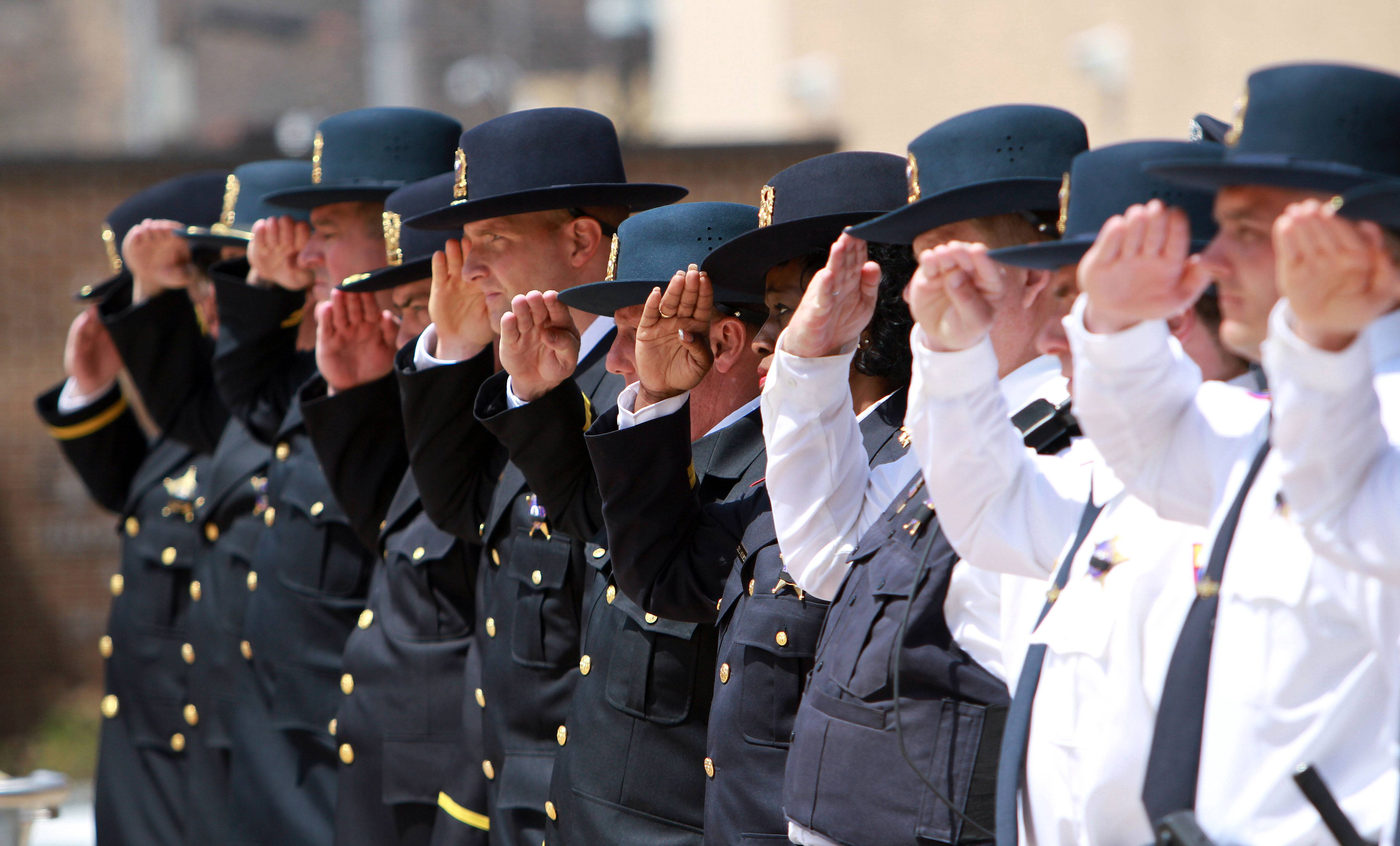Local police officers salute Friday during the Lake County Police Memorial at Lincoln Memorial Plaza in Waukegan. The ceremony honored 17 officers from Lake County who have died in the line of duty since 1894.