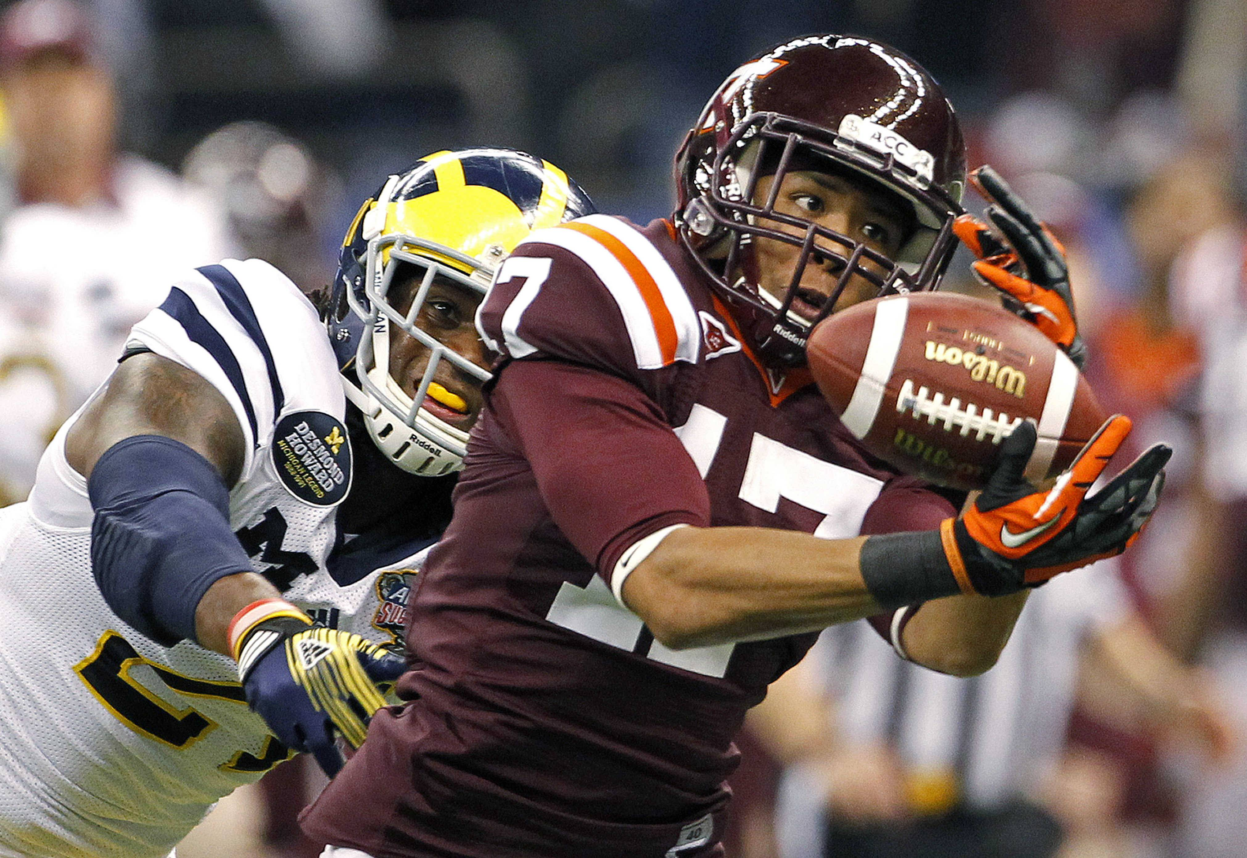 Virginia Tech cornerback Kyle Fuller (17) intercepts a pass intended for Michigan wide receiver Junior Hemingway (21) during the first quarter of the Sugar Bowl NCAA college football game in New Orleans, Tuesday, Jan. 3, 2012.