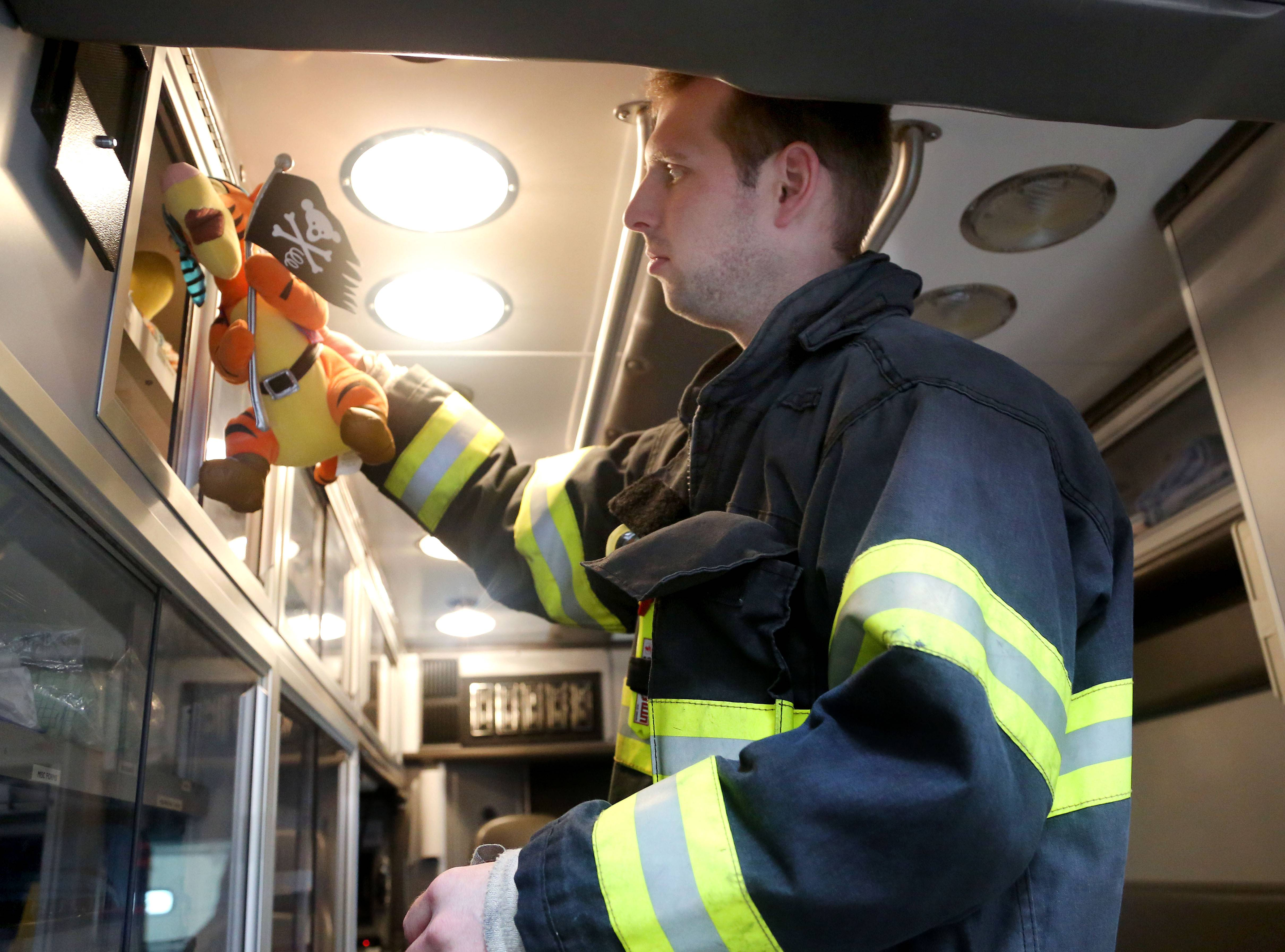 Libertyville firefighter Brian Bagdon loads stuffed animals into an ambulance. The animals were donated by Libertyville chiropractor Dr. Tom Bennett, who collected them from his patients. The animals are given to kids on emergency calls.
