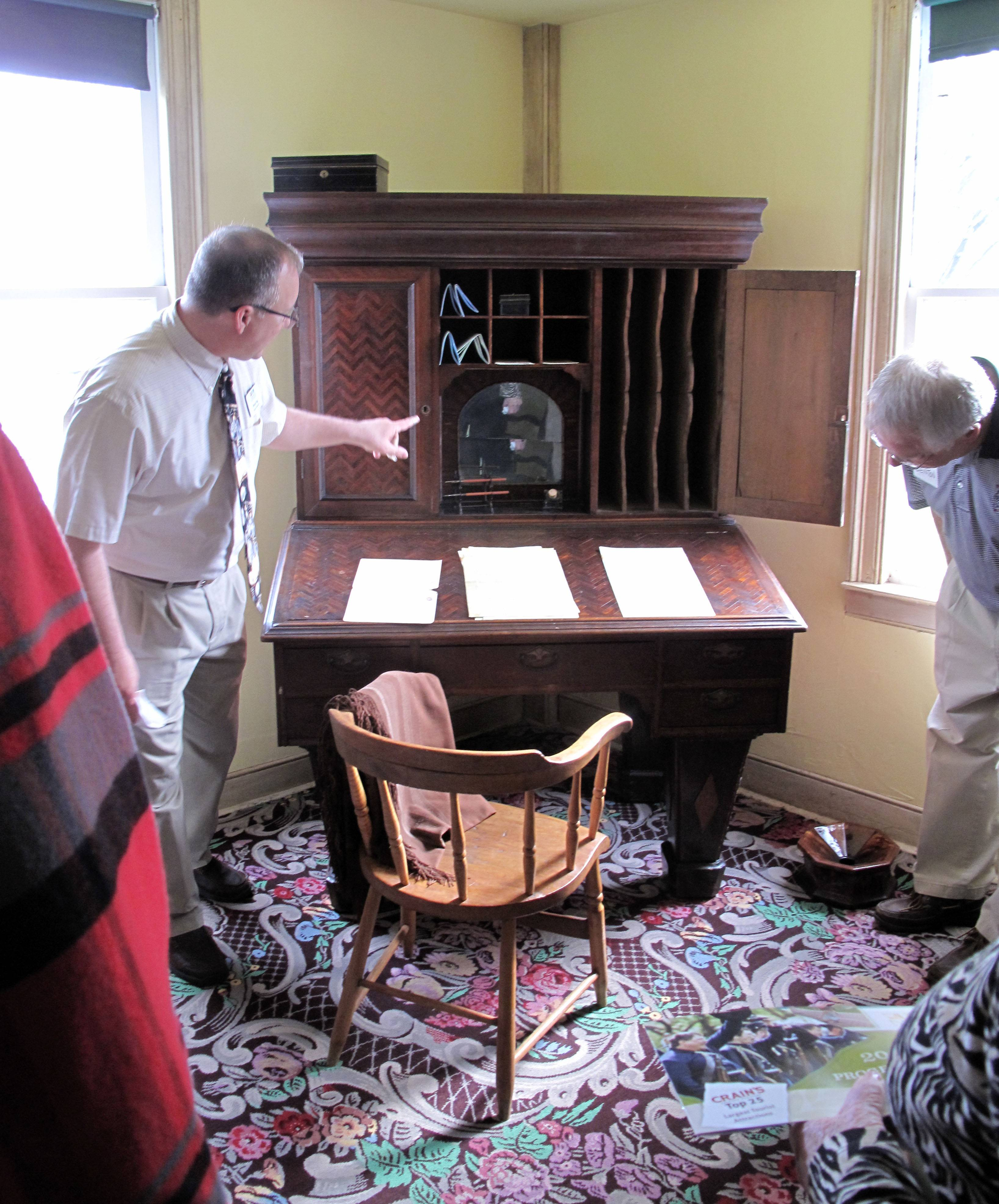 During a tour Thursday of the newly rededicated Hobson Law Office at Naper Settlement, Curator of Research Bryan Ogg shows how lawyers in the mid-1800s used compartments in their desks to file away important documents.