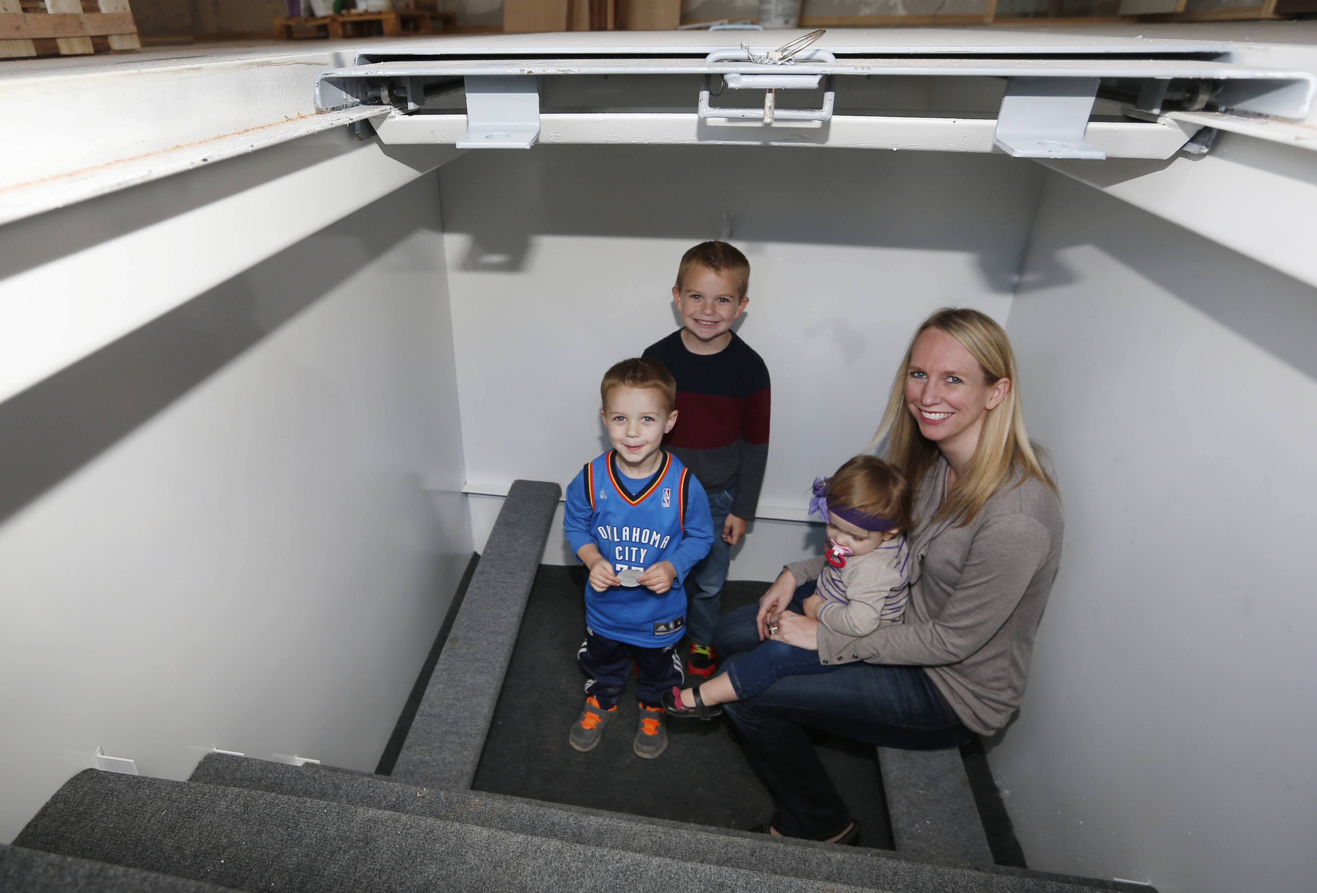 Tessa Beaulieu poses for a photo in the storm shelter in her new construction home with her children, from left, Hudson, Dawson and Sloane, in Edmond, Okla. Last year's deadly tornadoes, which killed more than 30 people, scared Oklahomans in a way that previous storms had not, moving them to add tornado shelters or reinforced safe rooms to their homes.
