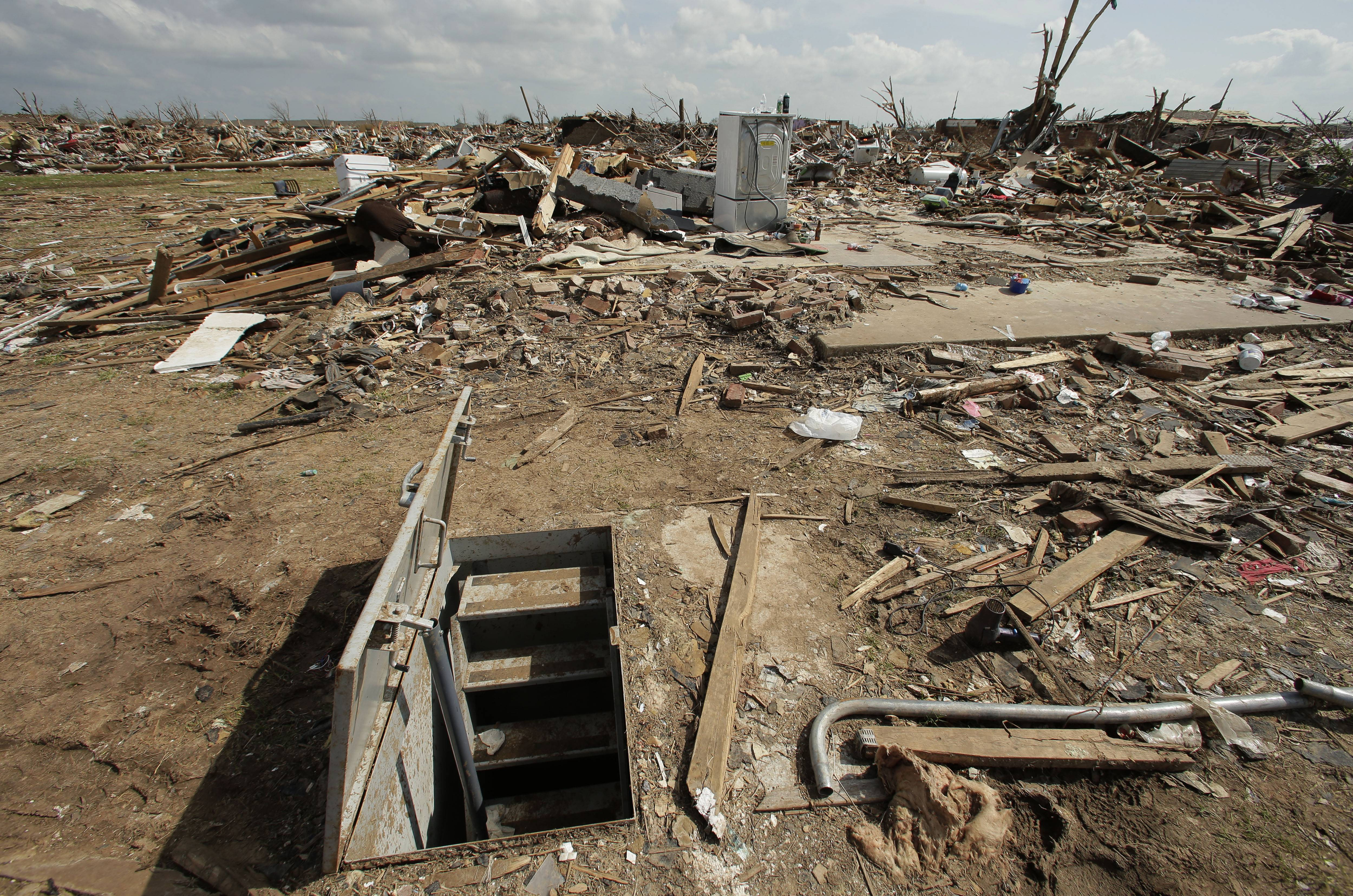 In this May 26, 2013, file photo, an underground shelter is seen near tornado rubble in Moore, Okla. The deadly tornadoes that killed more than 30 people scared Oklahomans in a way that previous storms had not, moving them to add tornado shelters or reinforced safe rooms to their homes.