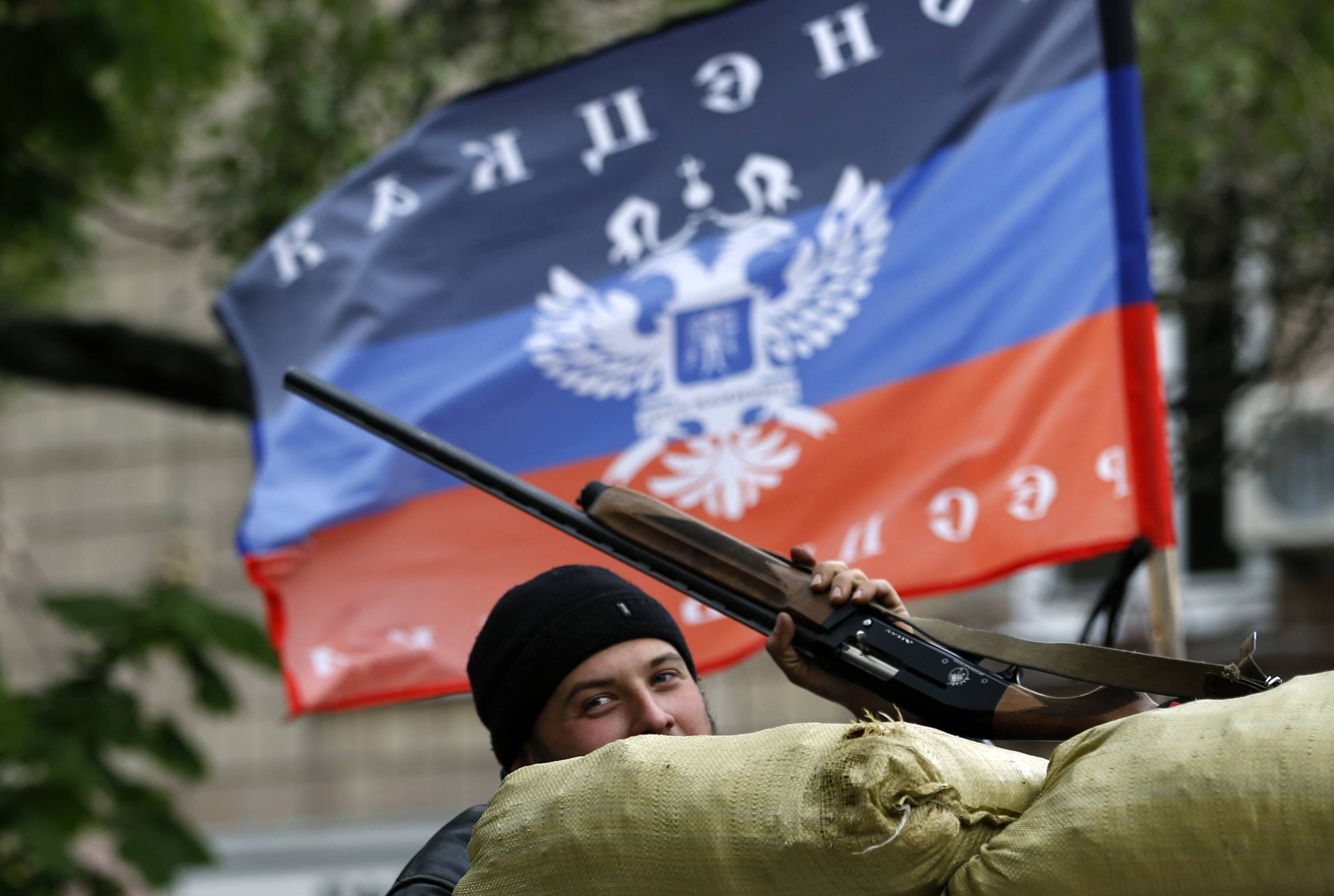 A pro-Russian gunman stands behind the barricades and shows his hunting rifle in front of the flag of the self-proclaimed Donetsk People's Republic, in the center of Slovyansk, eastern Ukraine, Thursday. A strong majority of Ukrainians want their country to remain a single, unified state and this is true even in the largely Russian-speaking east where a pro-Russia insurgency has been fighting for autonomy, a poll released Thursday shows.