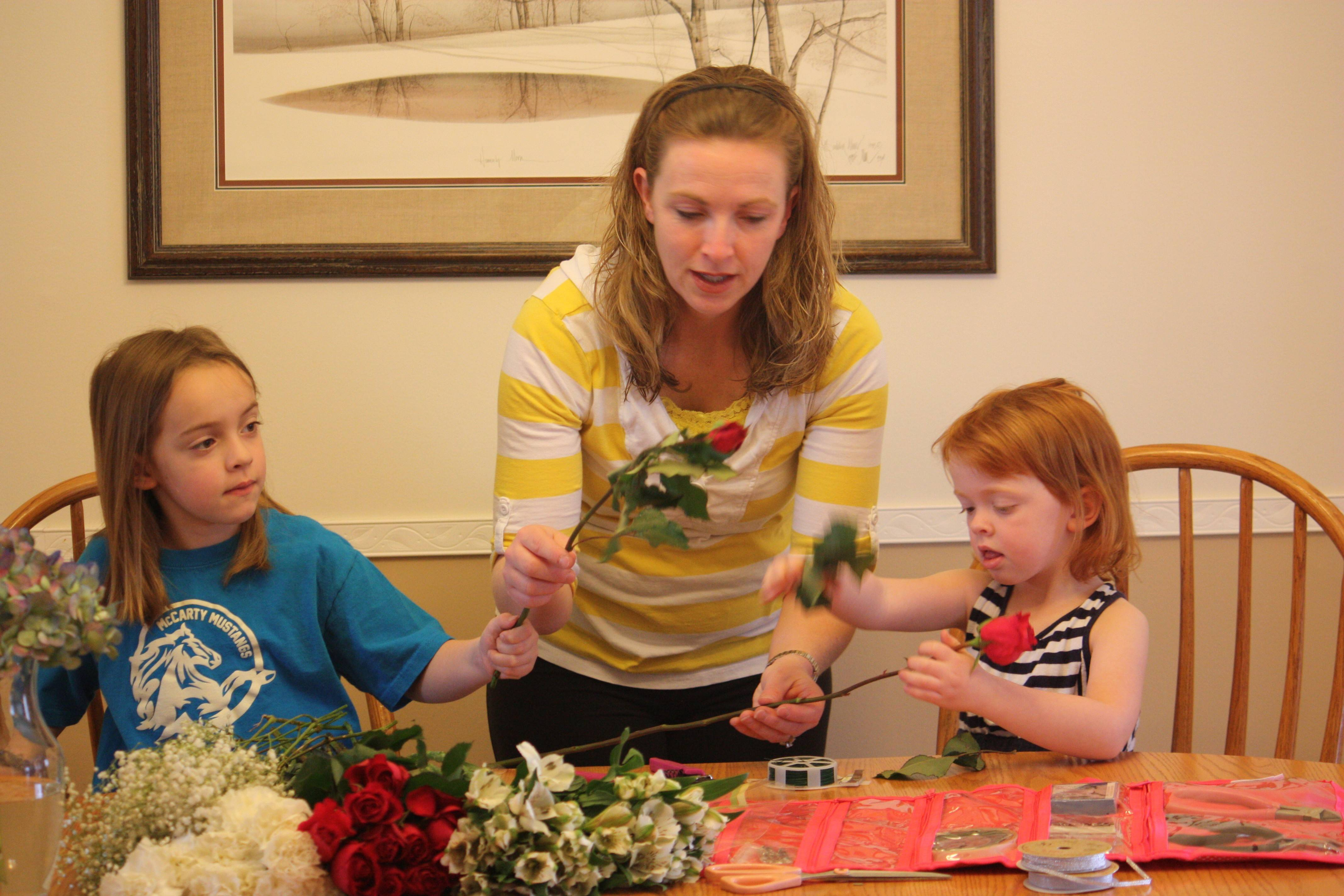 "Jen Byers of Naperville makes an arrangement for a customer of her Flowers by Jen consulting service with her daughters, Katie, 6, and Karly, 4. Byers says starting her own business allows her to create her own schedule and fit in work while still having enough ""mom time."""