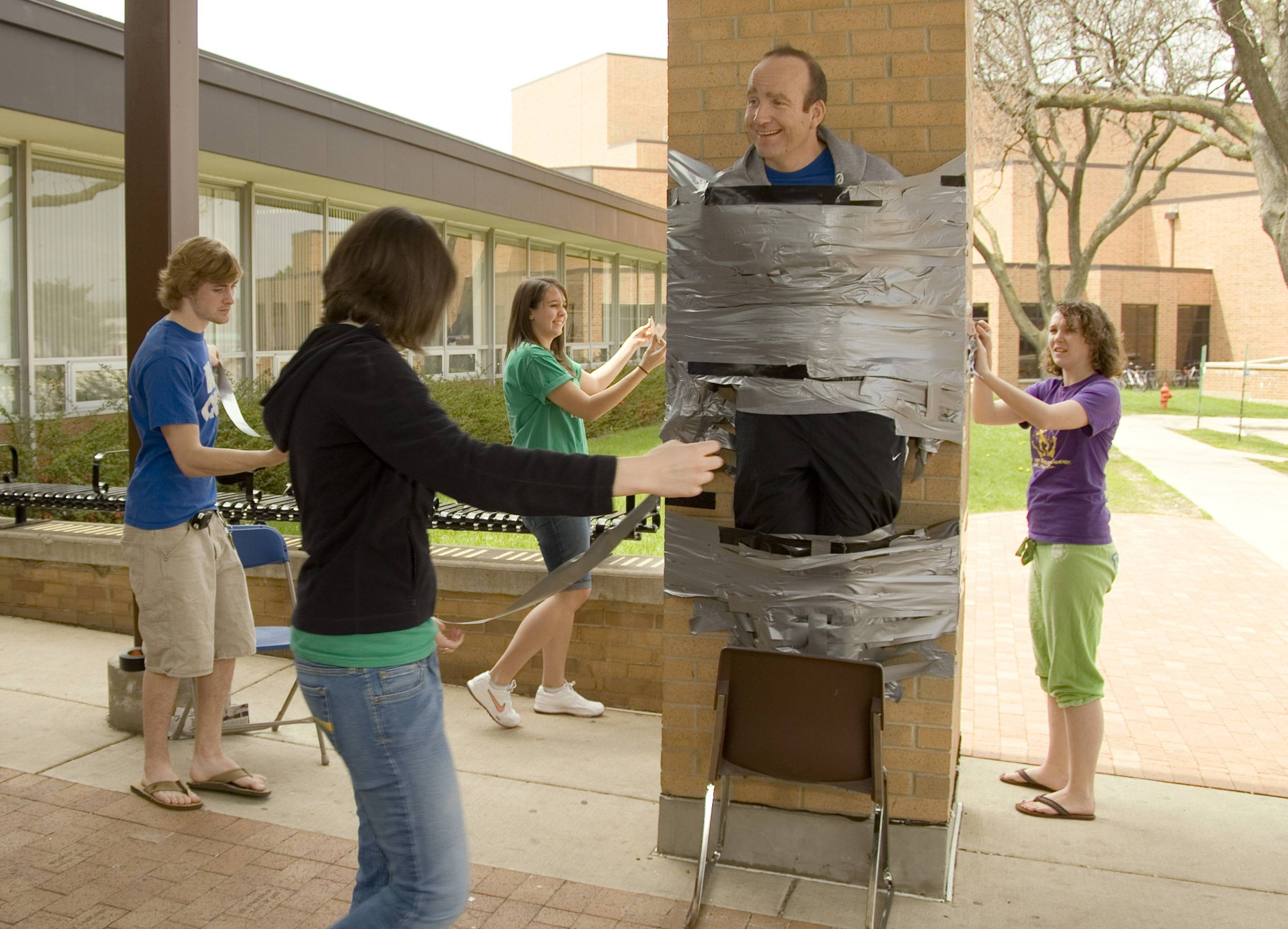 "Larkin High School dean Christopher Capps volunteered to be the ""in-duct-tee"" during the 2008 Connie-A-Thon fundraiser. Students paid 50 cents per foot of duct tape to help mount Capps to a pillar at the Elgin school's main entrance."