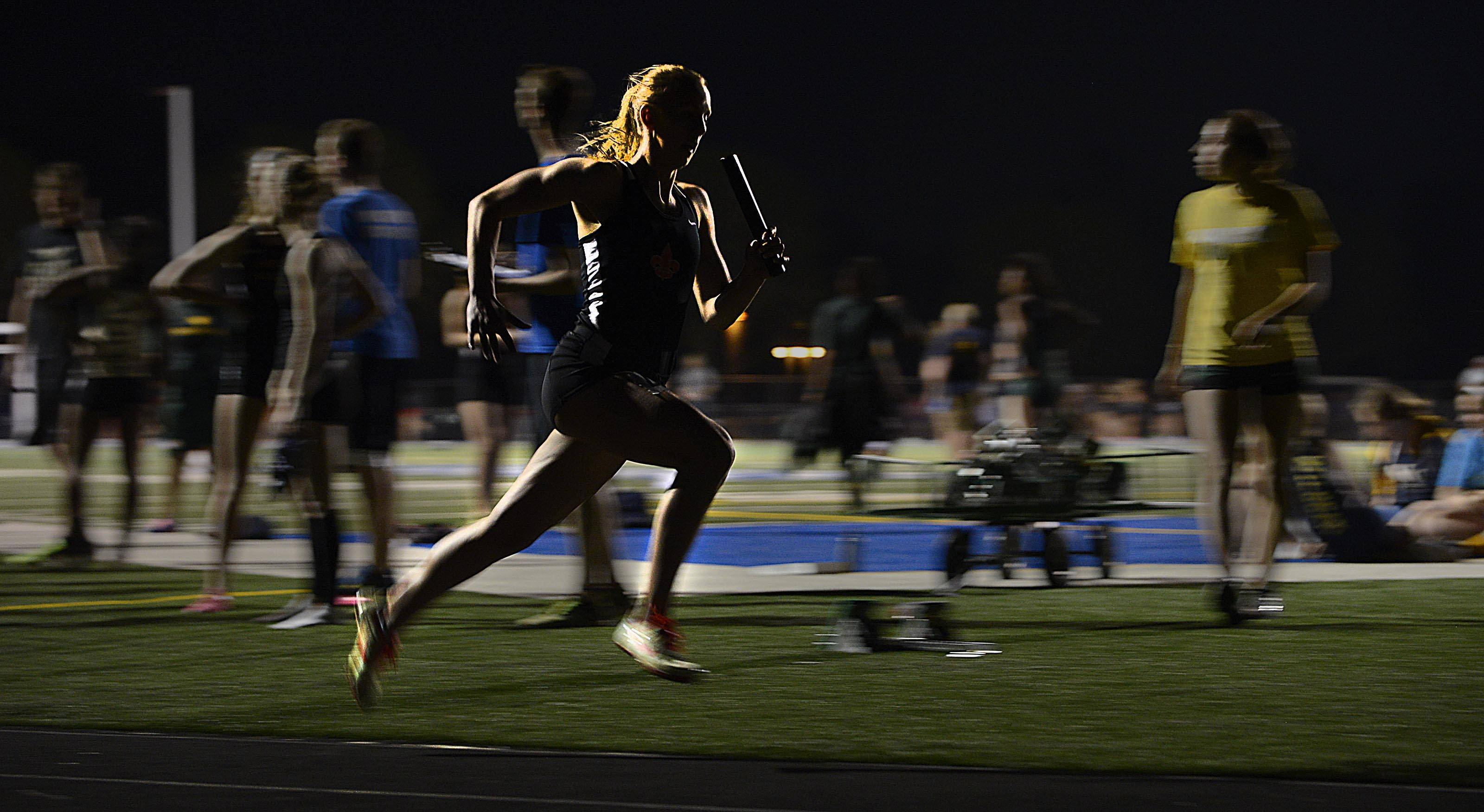 Backlit by the stadium lights, St. Charles East's Elizabeth Chmelik streaks around turn one of her anchor leg of the winning 4x400 meter relay Thursday at the Upstate Eight Conference girls track meet at Geneva High School. The relay team set a personal best time and the Saints won the meet.
