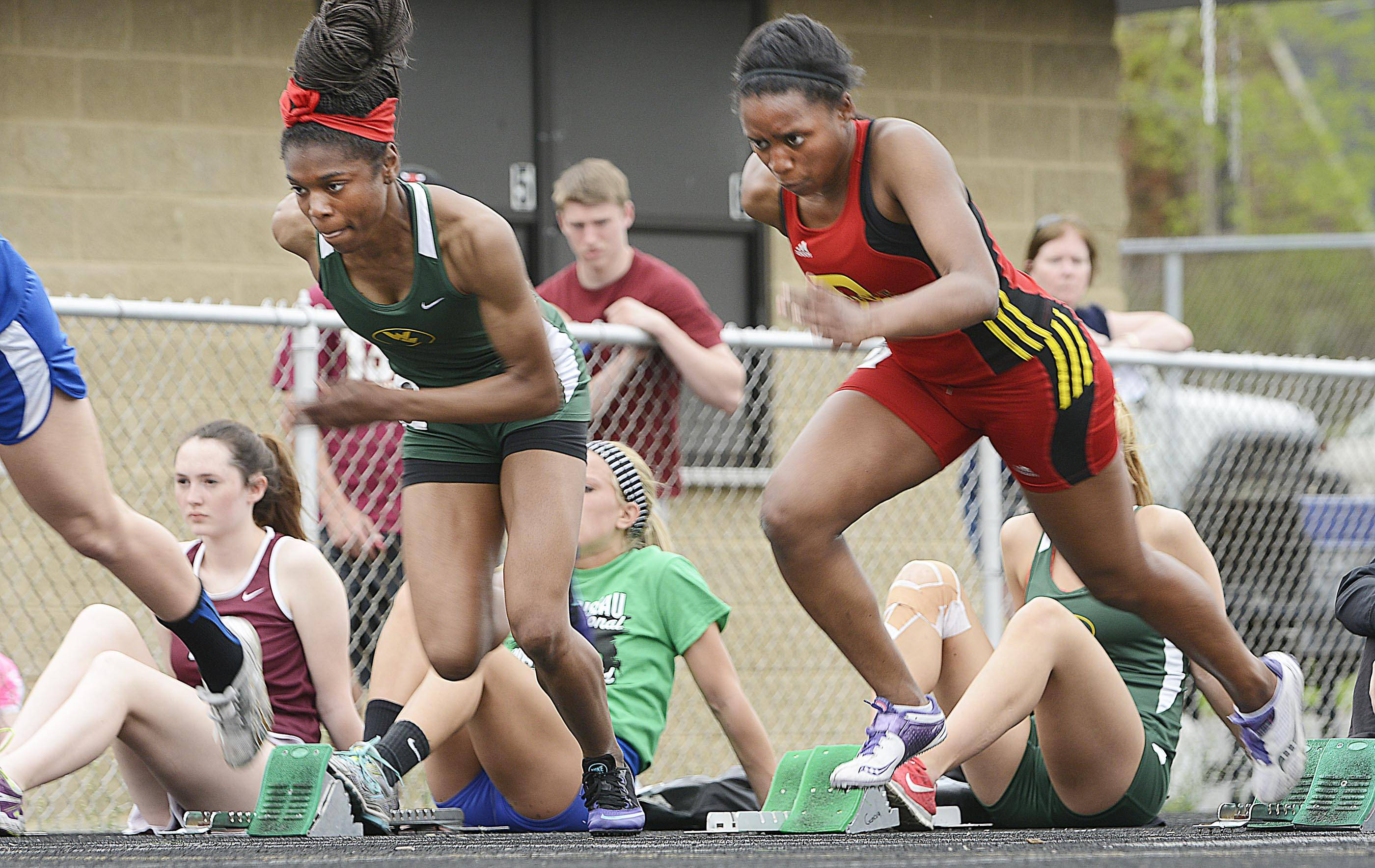Batavia's Hannah Schlaman, right, and Waubonsie Valley's Tatiana Moore, push out of the blocks in the 100 meter dash Thursday at the Upstate Eight Conference girls track meet at Geneva High School.