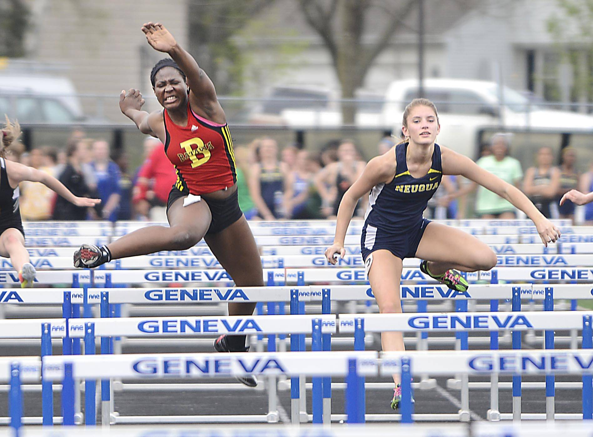 Batavia's Leah Narup loses her steps and gives the lead to Neuqua Valley's Kenna Lonergan, who won the 100 meter hurdles Thursday at the Upstate Eight Conference girls track meet at Geneva High School.