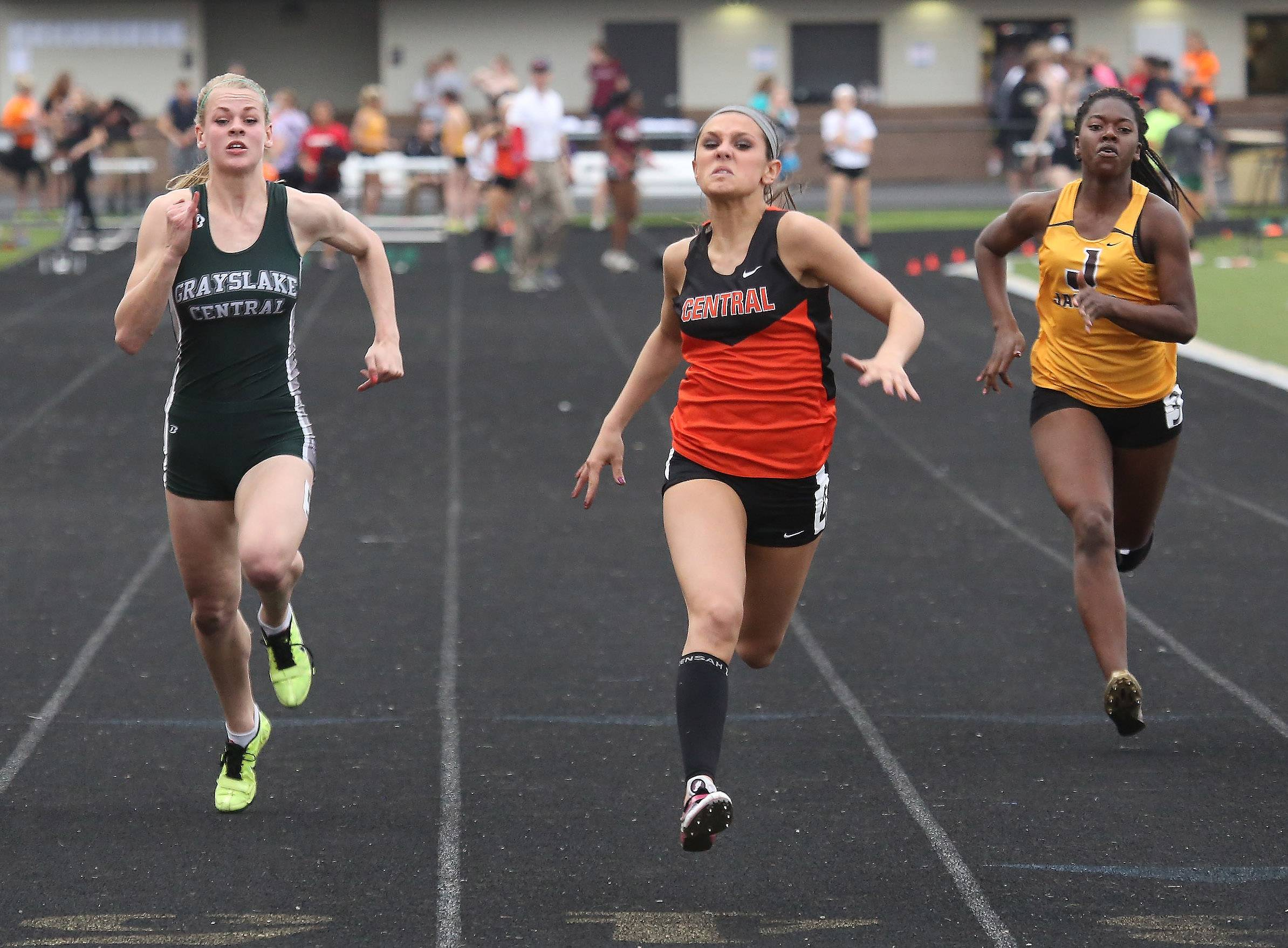 Crystal Lake Central sprinter Celeste Madda wins the 100-meter dash with Grayslake Central sprinter Leah Kloss, left, and Jacobs sprinter Taylor Bradford, right, during the Fox Valley Conference meet Thursday at Grayslake North.