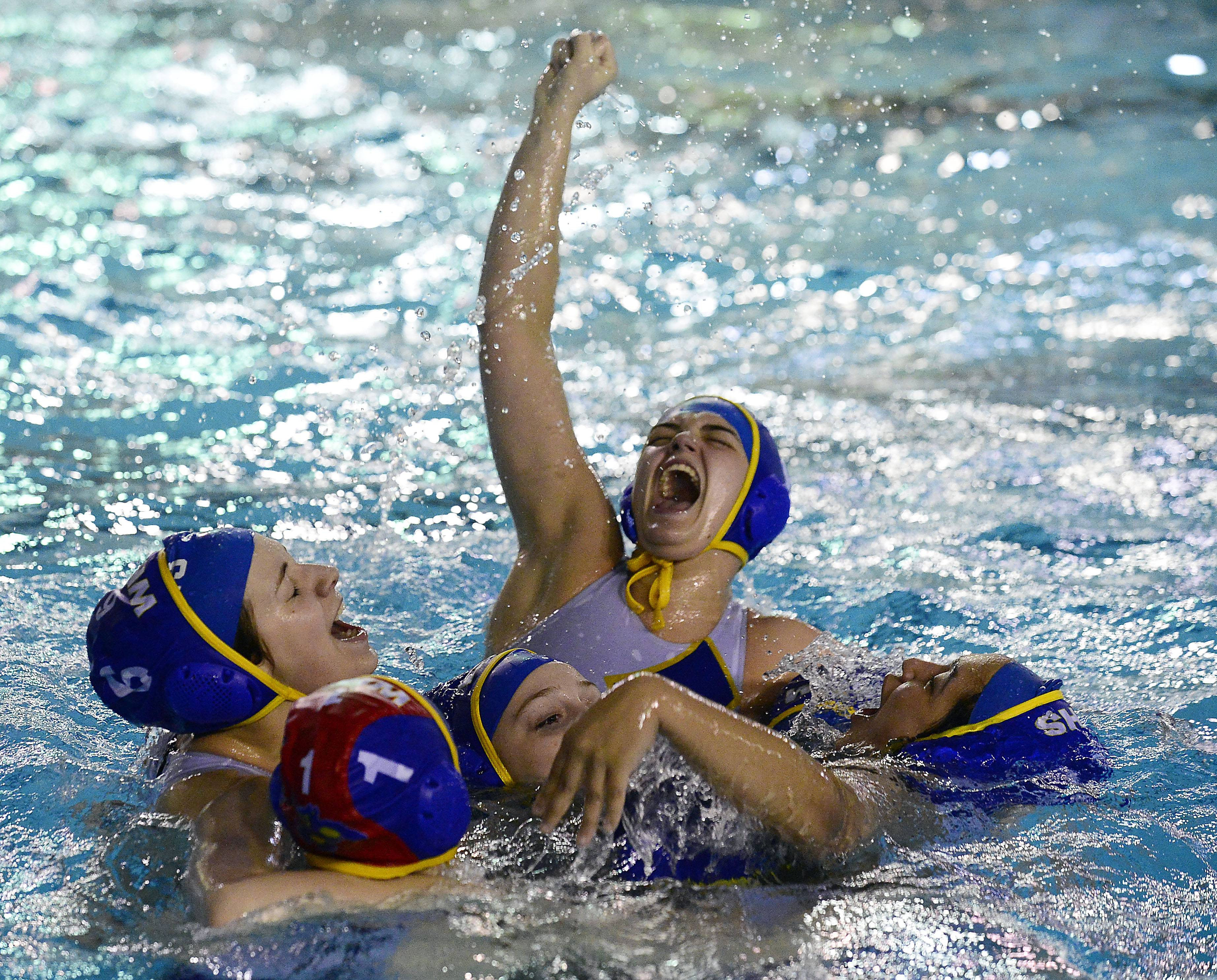 Wheeling's Theresa Godlewski, middle, and the rest of her teammates celebrate their overtime victory against Conant in the Mid-Suburban League's girls water polo championship game at Conant on Thursday.