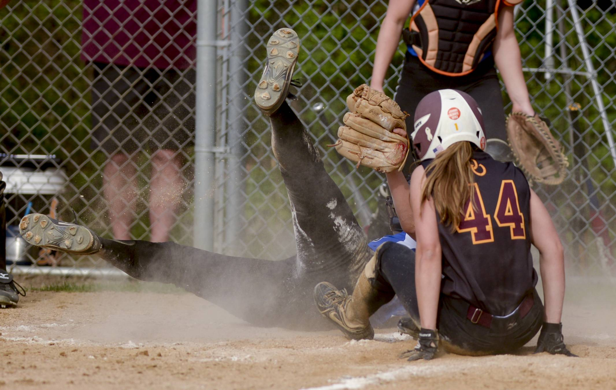 St. Francis' pitcher Maggie Remus hits the ground while covering home plate as Montini's Lauren Trojnar scores during softball action in Wheaton Thursday.