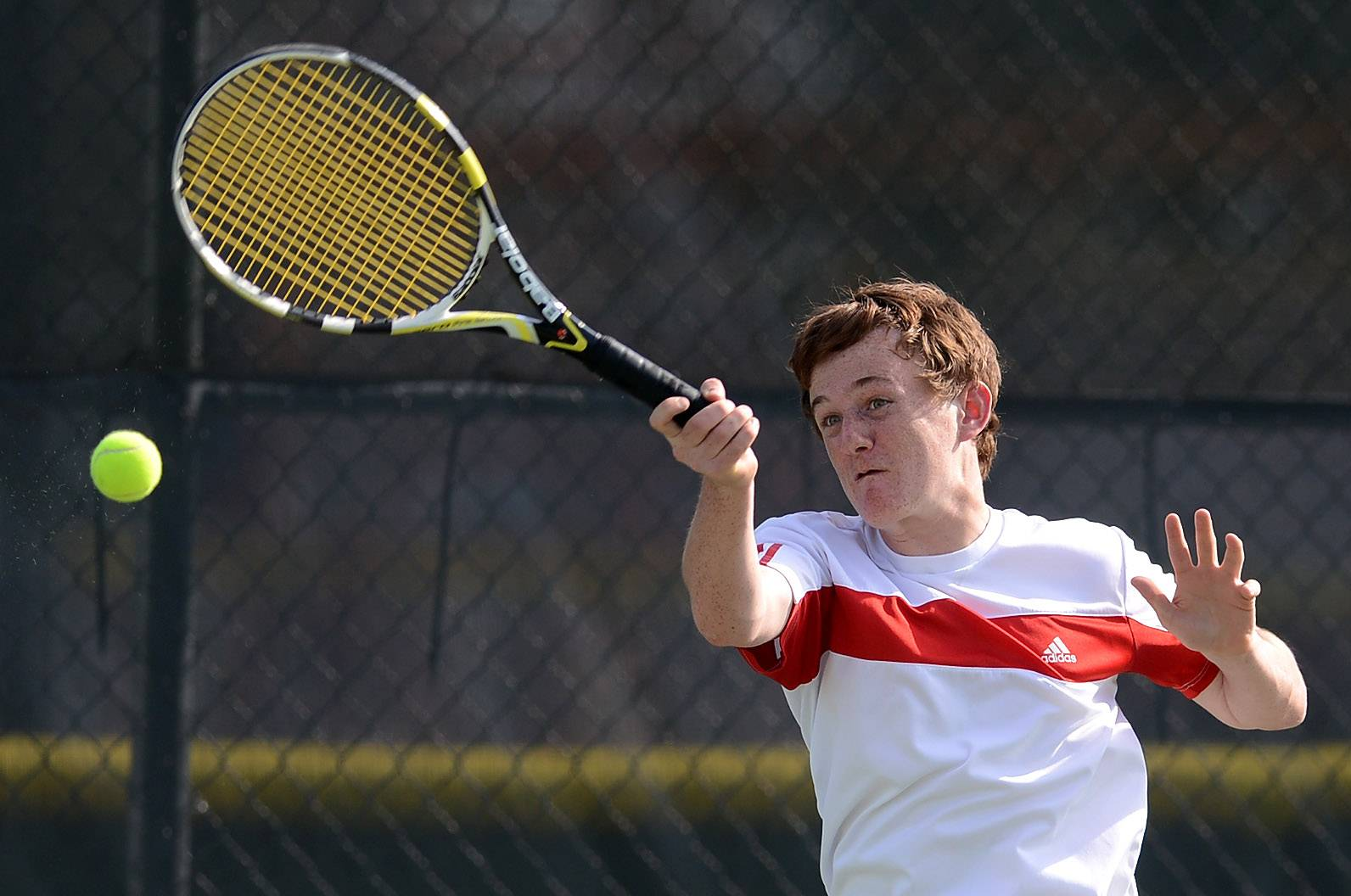 Adam Maris of Batavia returns serve in the #1 doubles match against St. Charles North during tennis action at Batavia Thursday.