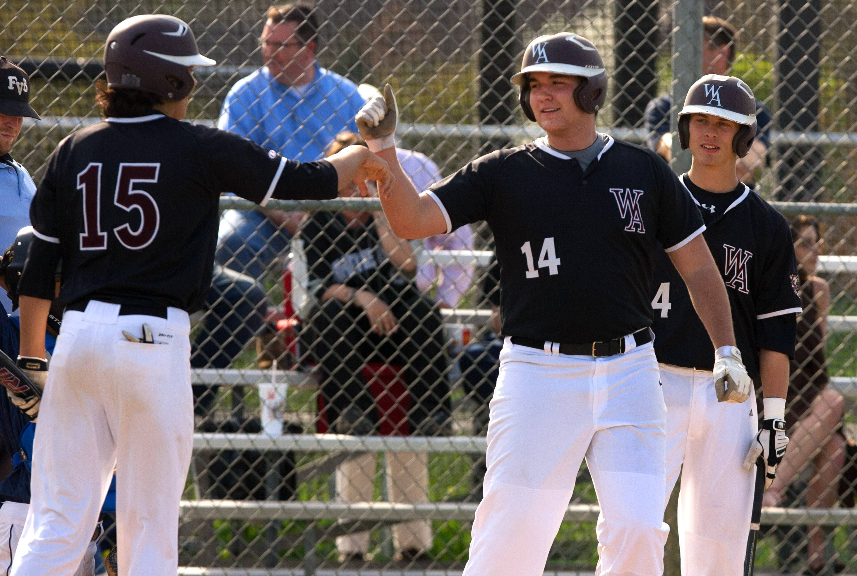 Wheaton Academy's Ryan Beck, center, crosses home plate after hitting his first of two three-run homers against IC Catholic Prep during baseball action in West Chicago. Adam Ghosh, left, and Brett Albaugh, right, give Beck high fives.