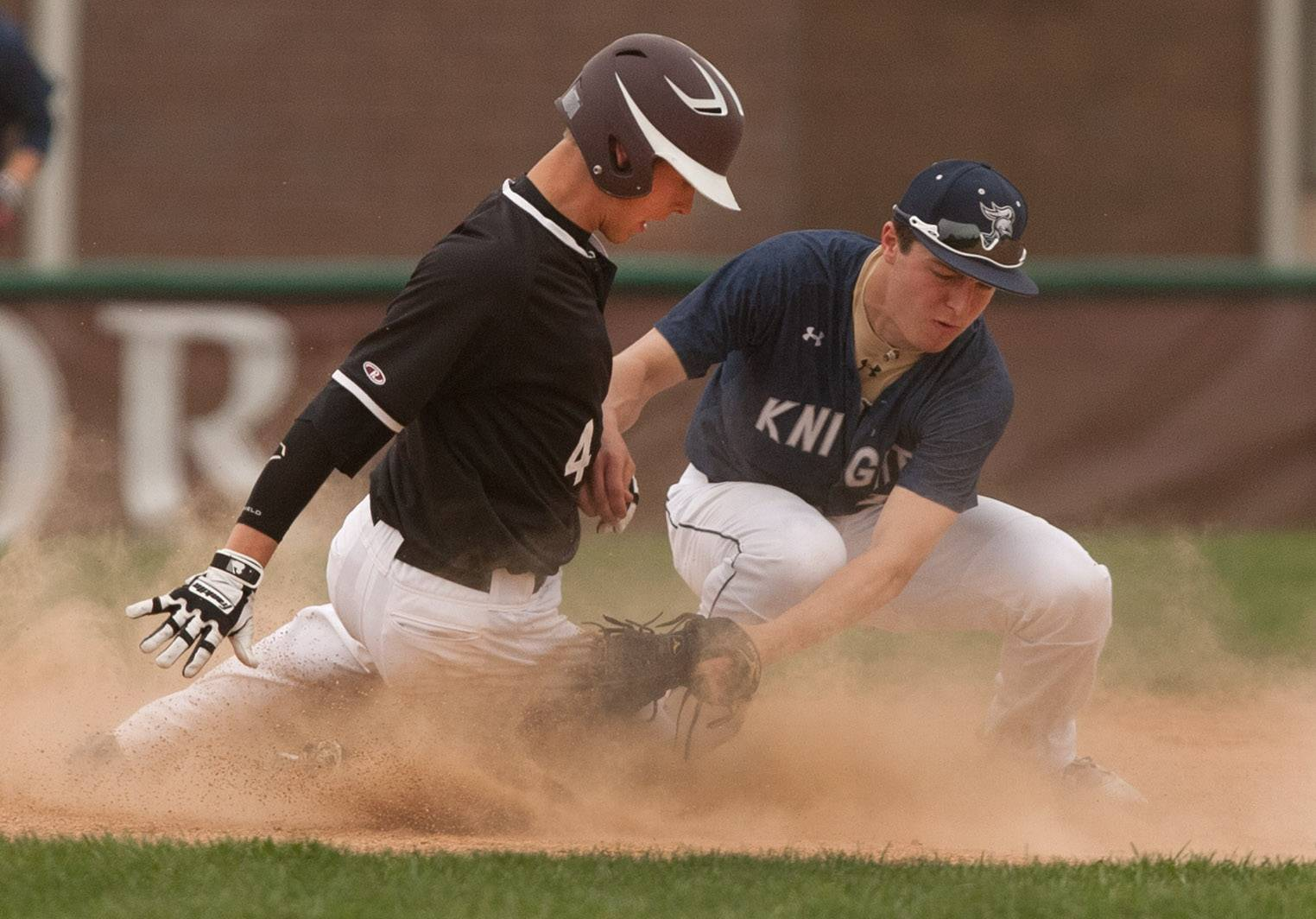 Wheaton Academy's Brett Albaugh slides safely into second base under the tag of IC Catholic Prep's Sean Sutton during baseball action in West Chicago.