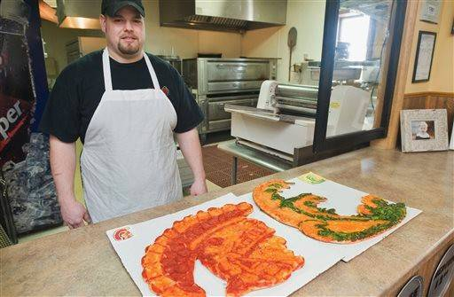 Trent Groothuis, owner of The Greathouse of Pizza in Casey, Ill., poses with some his unique pizza art.