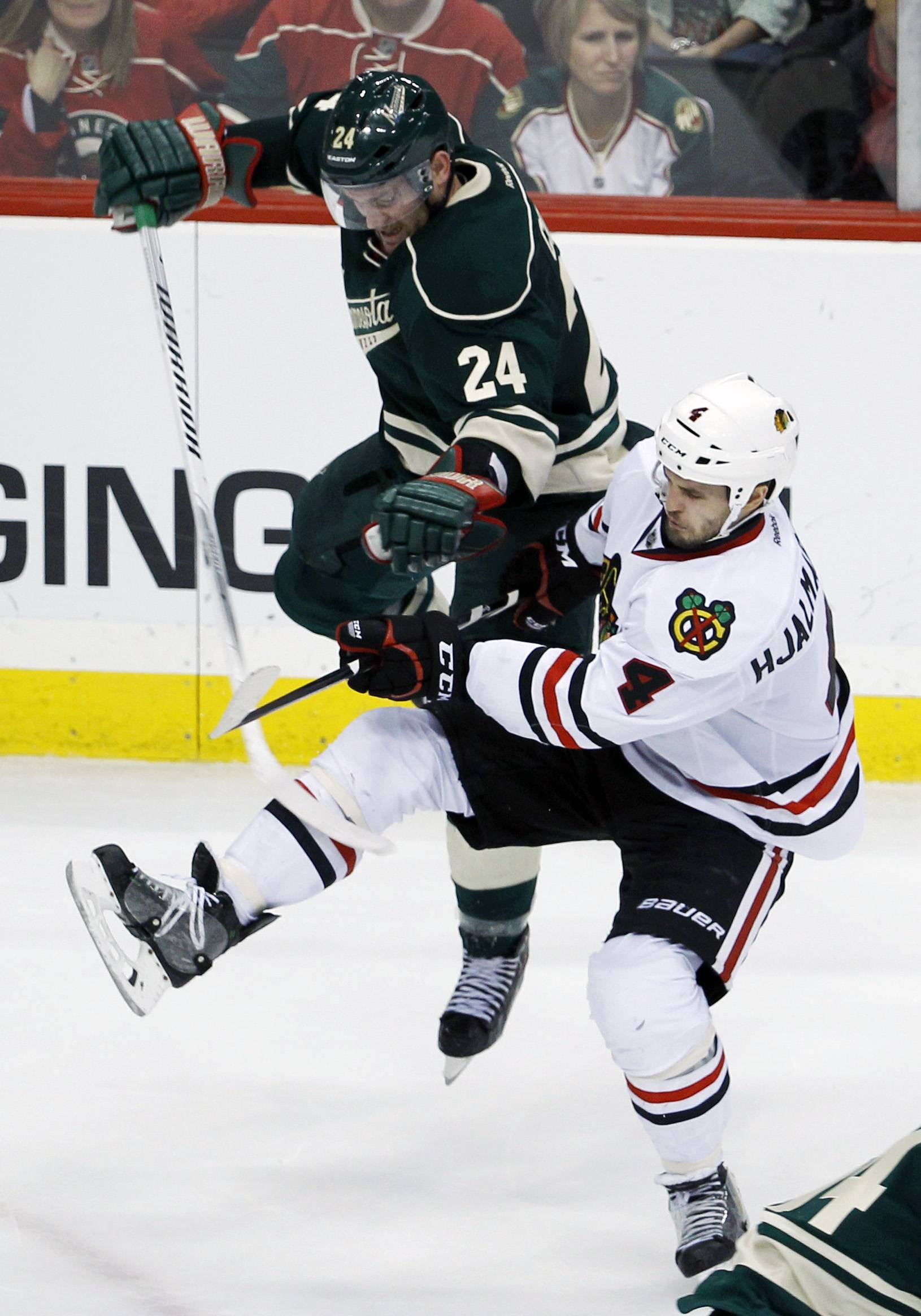 Minnesota Wild left wing Matt Cooke (24) and Chicago Blackhawks defenseman Niklas Hjalmarsson (4) collide during the third period of Game 4 of an NHL hockey second-round playoff series in St. Paul, Minn., Friday, May 9, 2014. The Wild won 4-2.