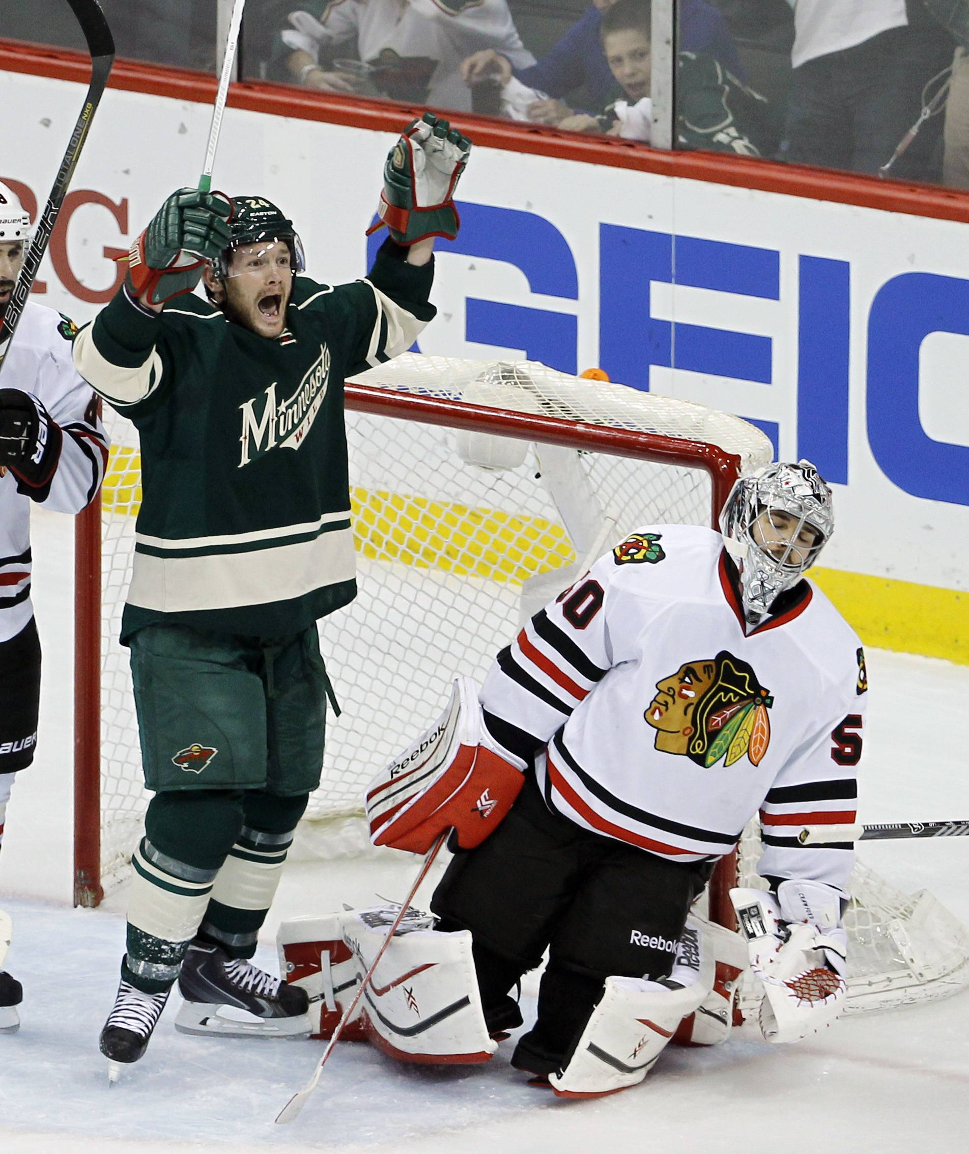 Minnesota Wild left wing Matt Cooke, left, celebrates after Wild right wing Justin Fontaine scored on Chicago Blackhawks goalie Corey Crawford, right, during the first period of Game 4 of an NHL hockey second-round playoff series in St. Paul, Minn., Friday, May 9, 2014.