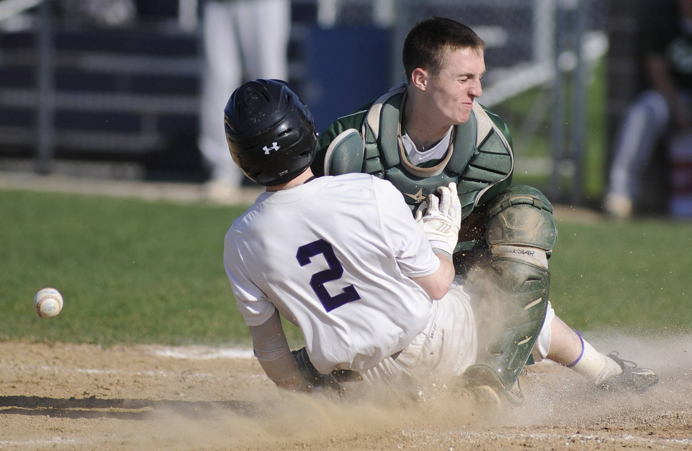 Hampshire's RJ Consigny slides into home plate safely, colliding with Grayslake Central catcher Sam Nozicka after the ball got past his mitt, hitting his leg and popping up in the second inning at Hampshire Friday.