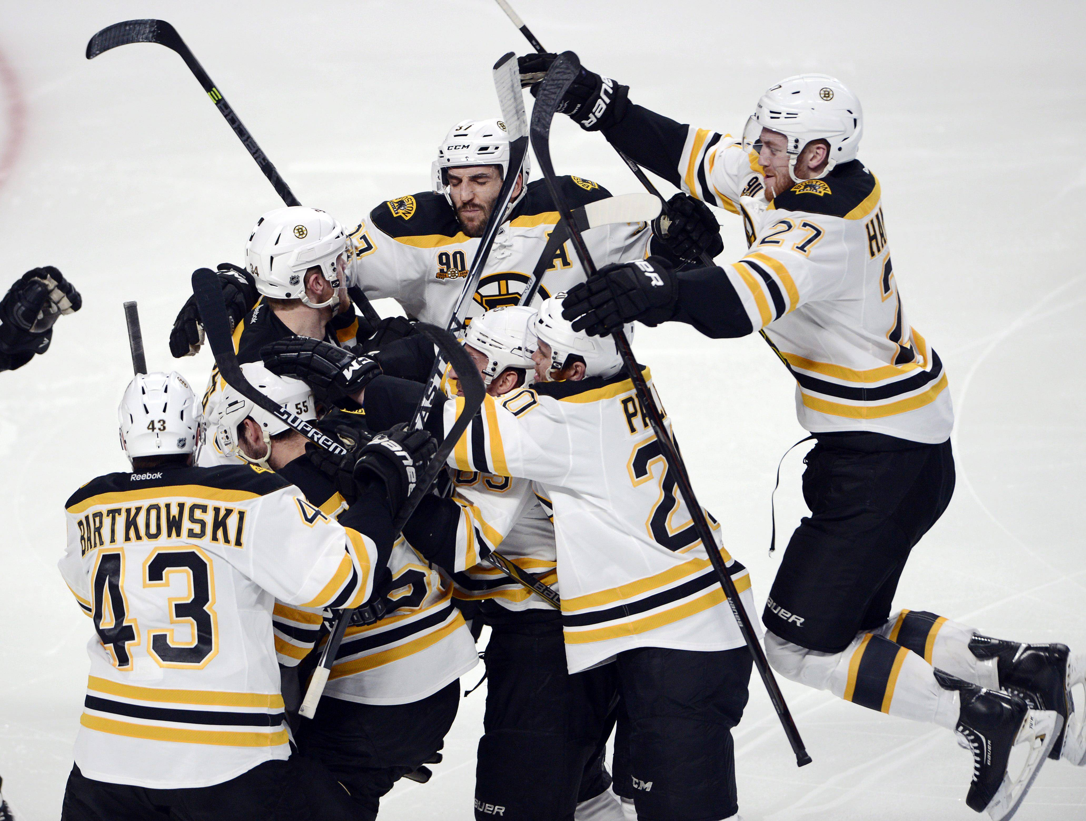 Boston Bruins' Matt Fraser is mobbed by teammates after scoring the game winning goal against the Montreal Canadiens during the first overtime period in Game 4 in the second round of the NHL Stanley Cup playoffs Thursday, May 8, 2014, in Montreal. (AP Photo/The Canadian Press, Ryan Remiorz)