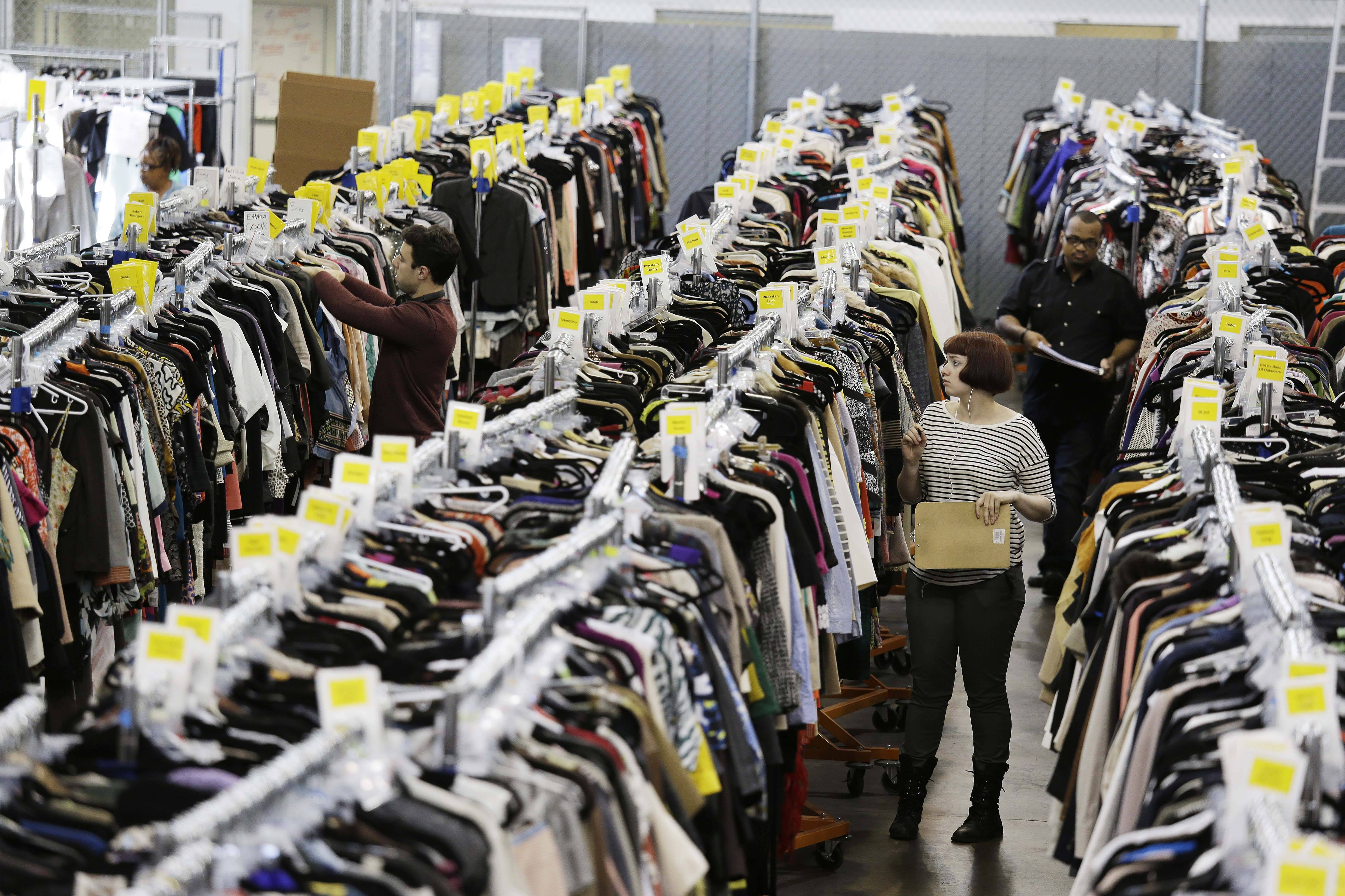 Workers locate and pull items for shipping from racks of designer clothing at the headquarters of The RealReal in San Francisco.