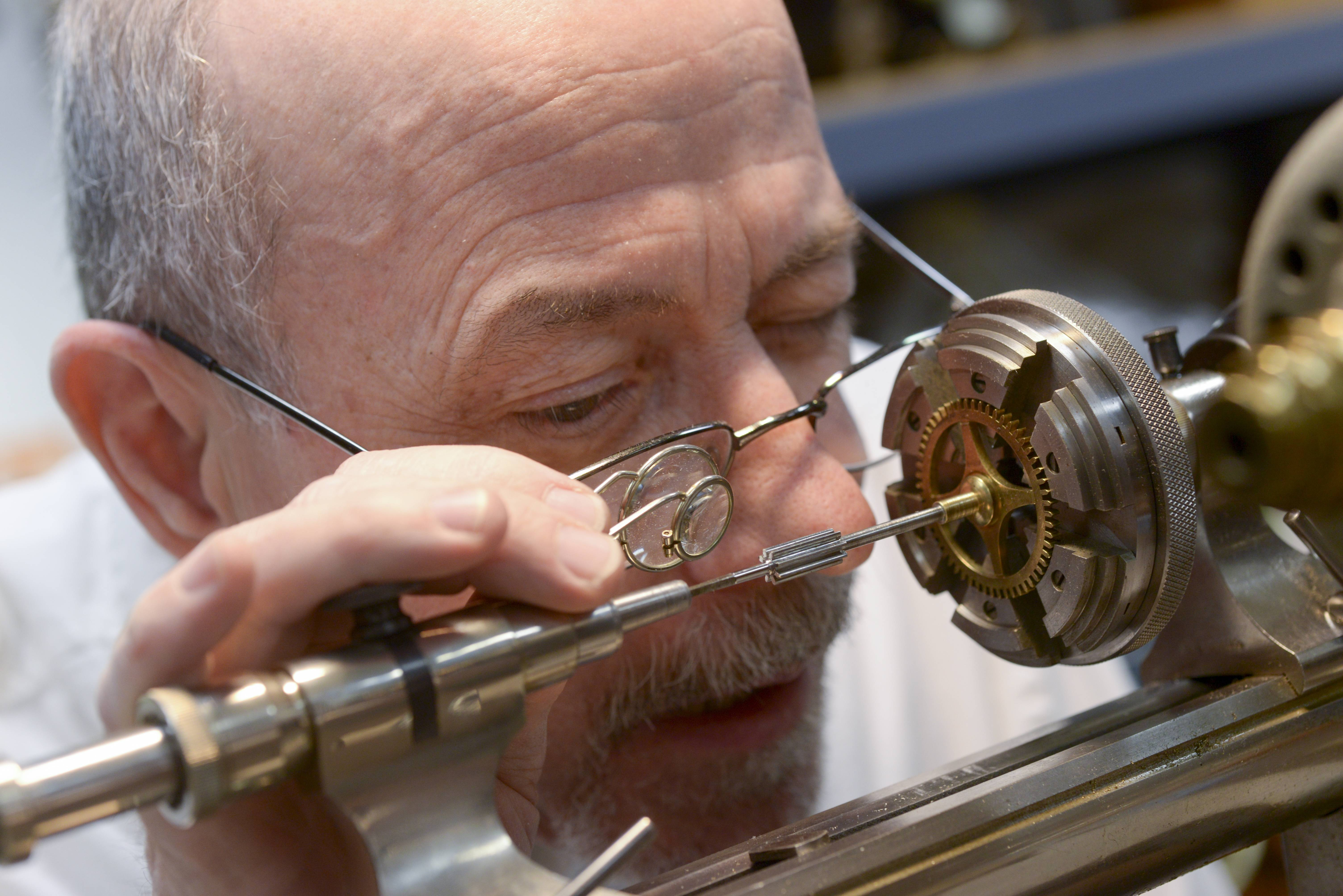 Certified master clockmaker Jim Lachapelle has to use a magnifying eyepiece to check the small and intricate parts of this 1890s clock.