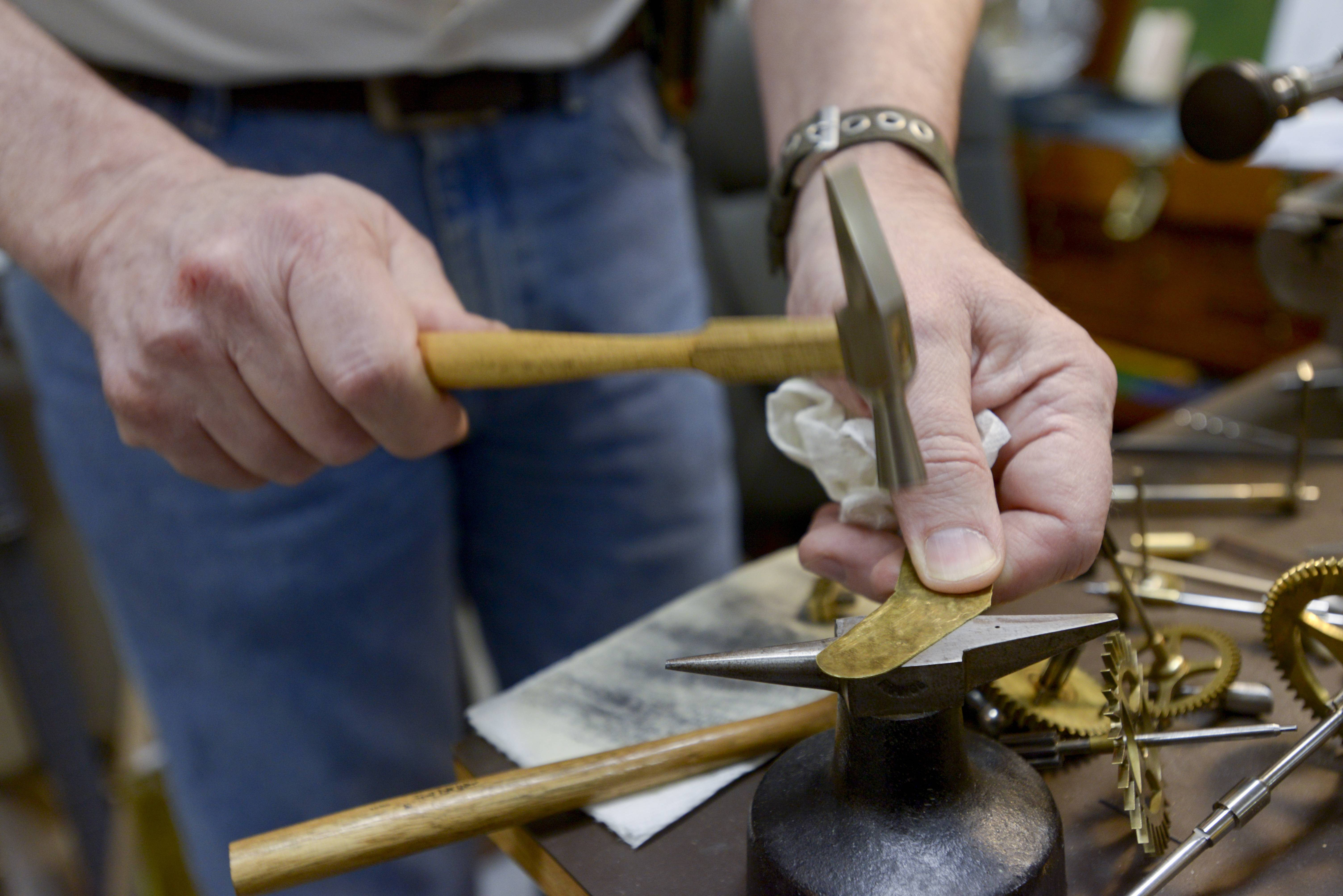 Lachapelle uses a mini anvil and hammer to temper a brass part of an antique clock.