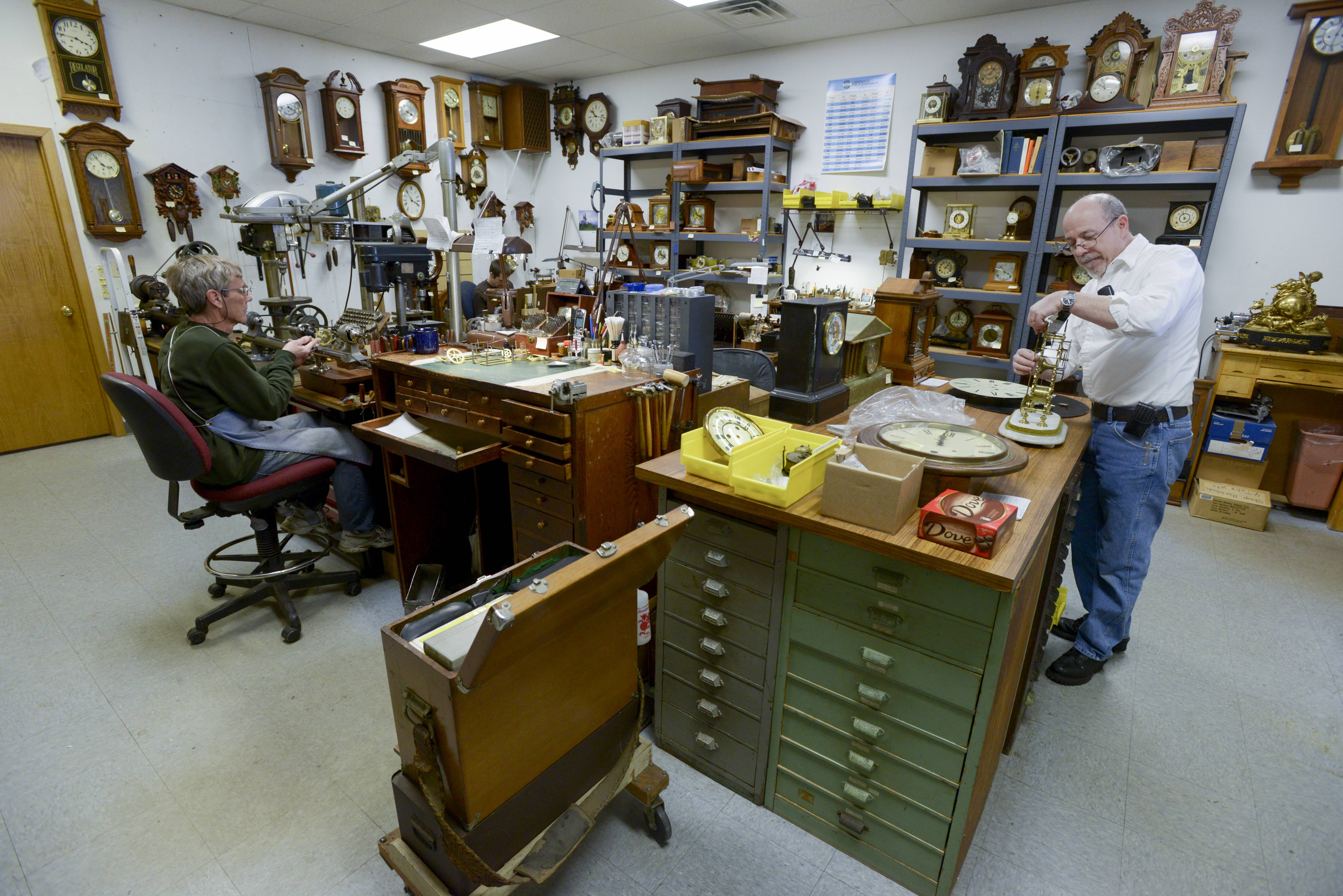 Jim Lachapelle, right, and his business parker Roland Iverson work on repairing clocks in their South Elgin store.