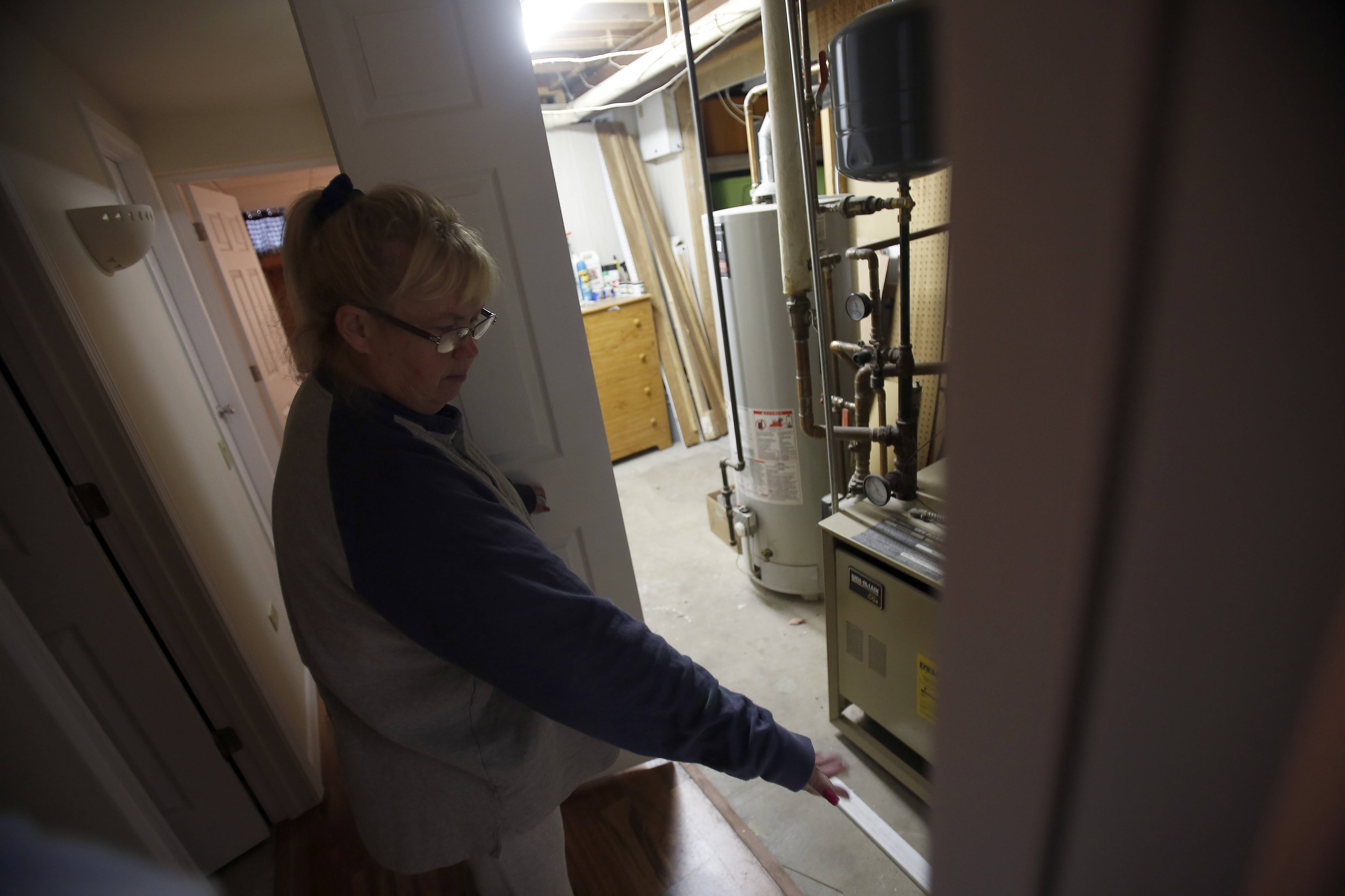 Marie Lagenbach points to an area near her furnace and water heater where she says sewer water came up.