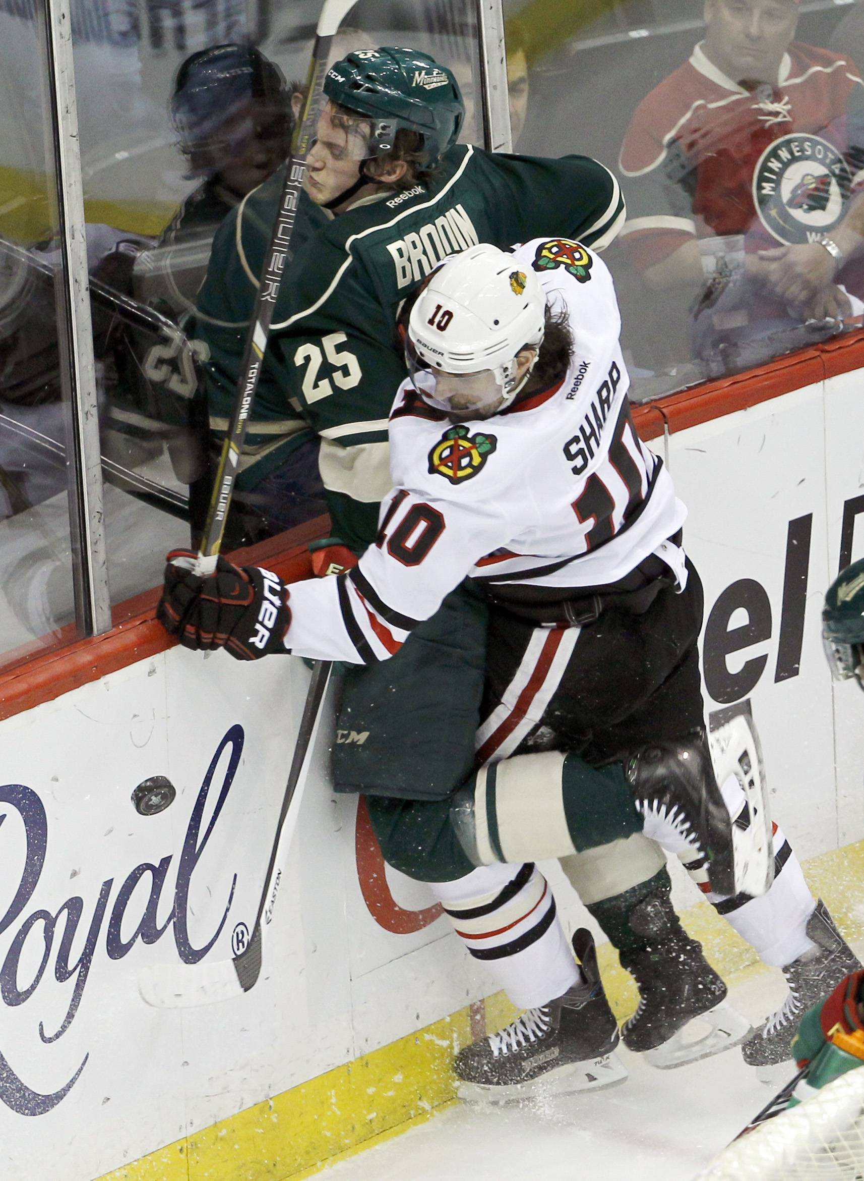 Patrick Sharp checks Wild defenseman Jonas Brodin into the boards as they battle for the puck during the first period of the Hawks' Game 4 loss Friday in Minnesota.
