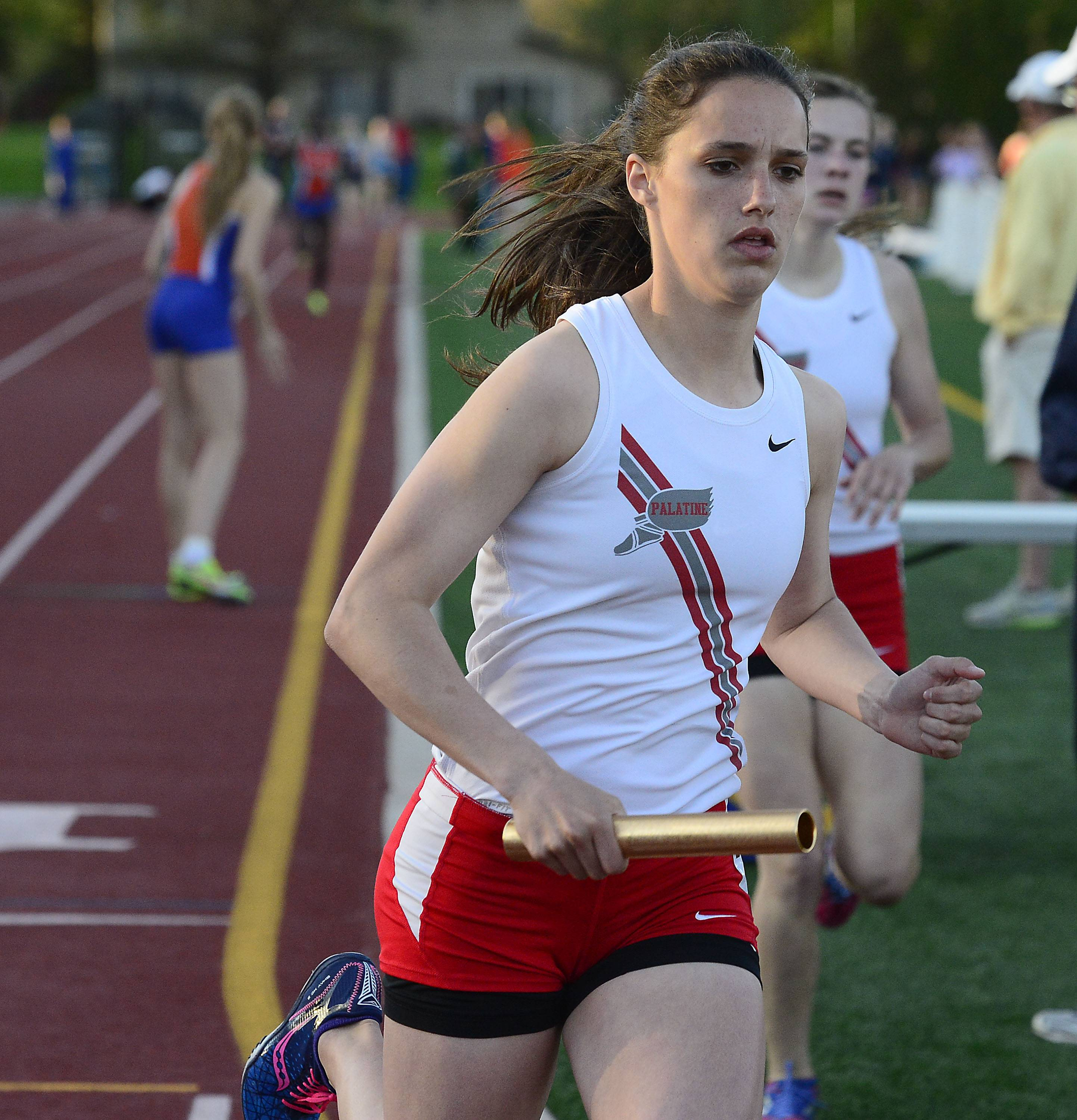 Palatine's Cassidy McPherson takes the handoff from teammate Kelly O' Brien in the 4x800 relay in the MSL meet at Wheeling on Friday.