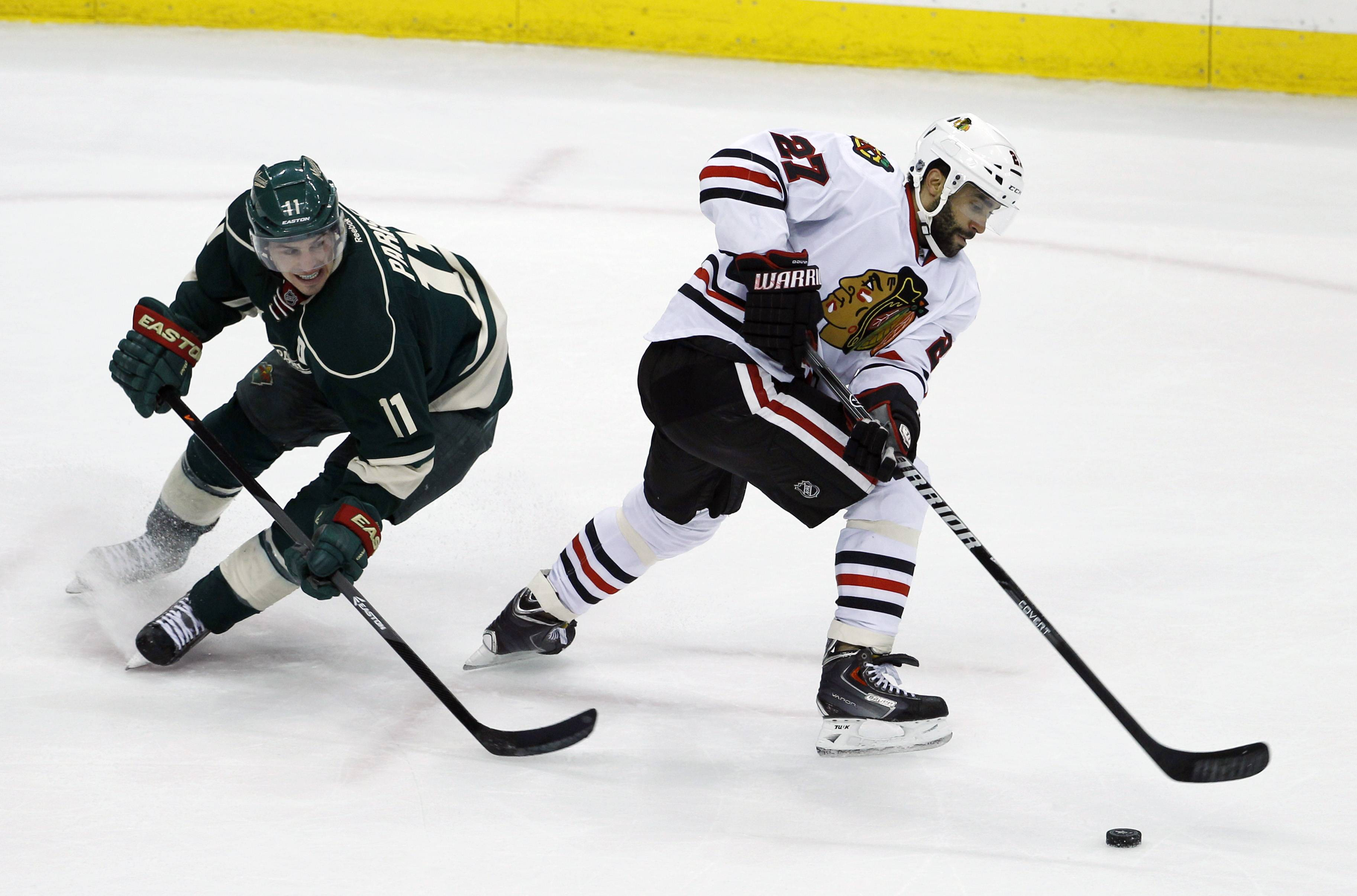 Chicago Blackhawks defenseman Johnny Oduya (27), of Sweden, steals the puck from Minnesota Wild left wing Zach Parise (11) during the second period.