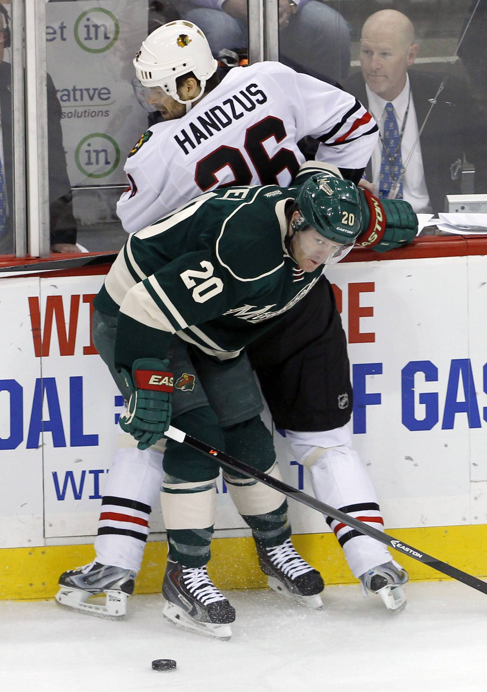 Minnesota Wild defenseman Ryan Suter (20) pins Chicago Blackhawks center Michal Handzus (26), of Czech Republic, into the boards and off the puck during the first period.