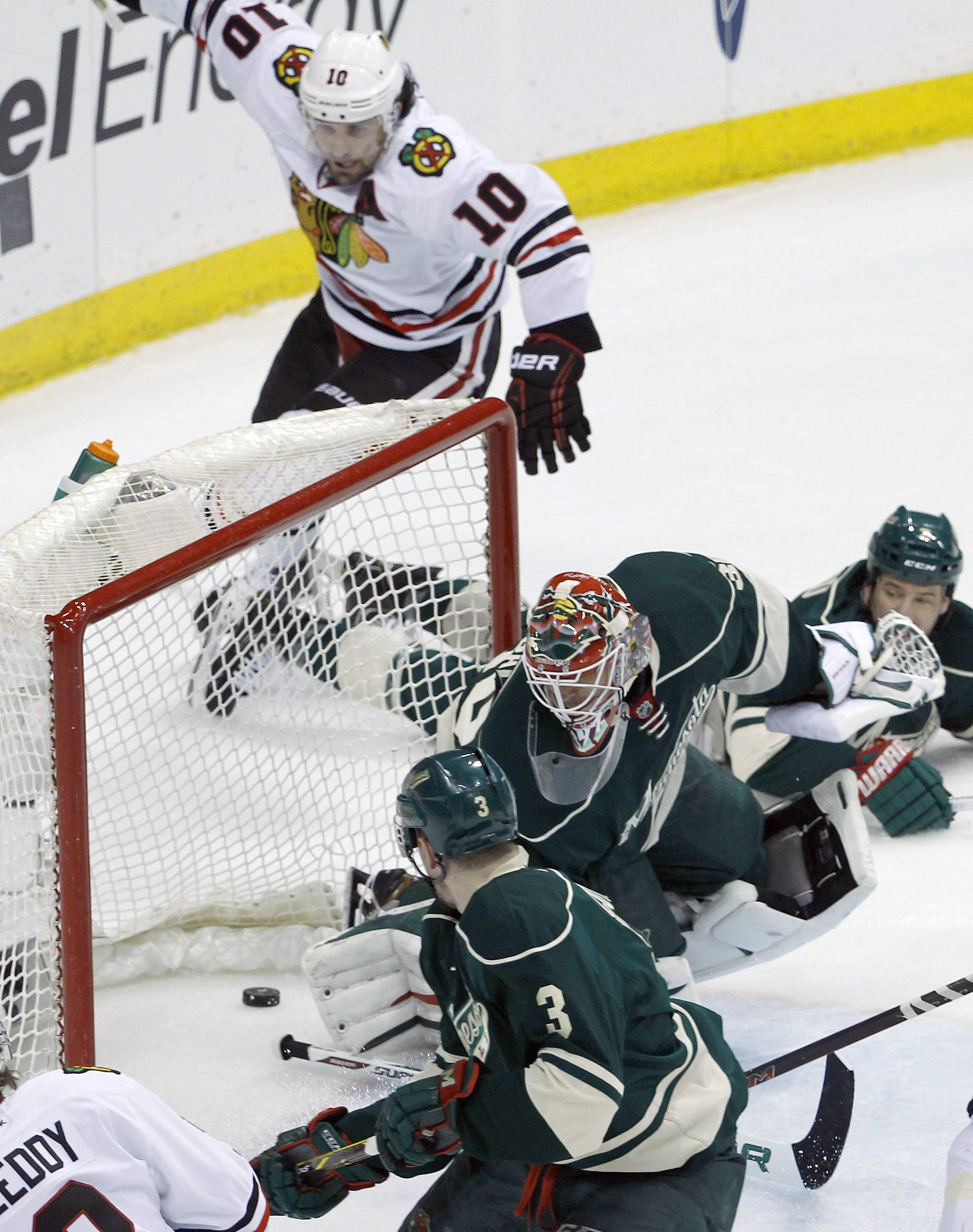Minnesota Wild goalie Ilya Bryzgalov, center, and Wild center Charlie Coyle (3) are near as a shot by Chicago Blackhawks left wing Patrick Sharp (10) goes in during the first period.