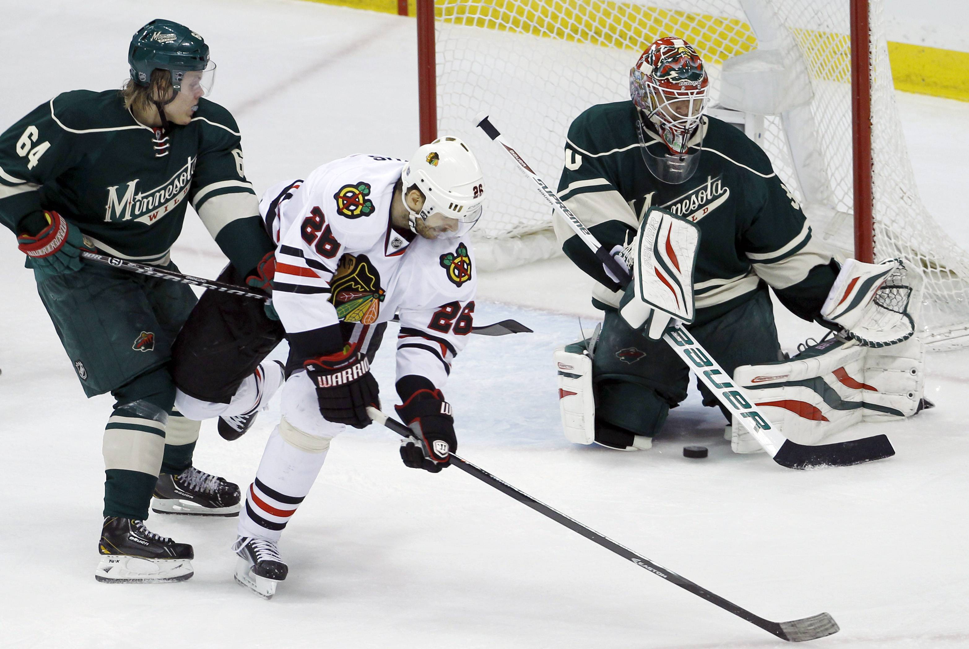 Chicago Blackhawks center Michal Handzus (26), of Czech Republic, gets a shot through the legs of Minnesota Wild goalie Ilya Bryzgalov, right, of Russia, to score in front of Wild center Mikael Granlund (64), of Finland, during the second period.