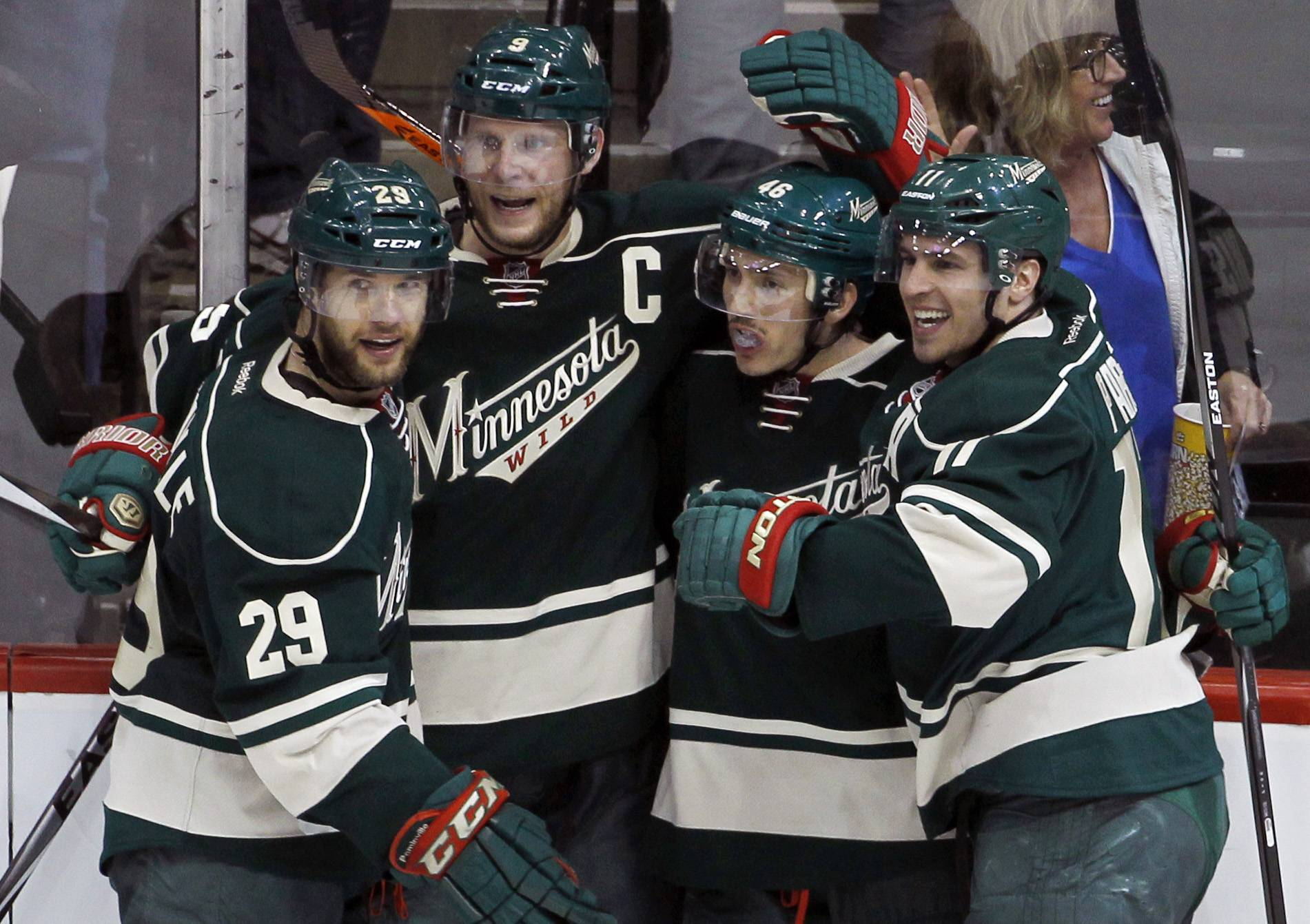 Minnesota Wild right wing Jason Pominville (29), center Mikko Koivu (9), of Finland, defenseman Jared Spurgeon (46) and Minnesota Wild left wing Zach Parise, right, celebrate after Spurgeon scored on Chicago Blackhawks goalie Corey Crawford during the third period.