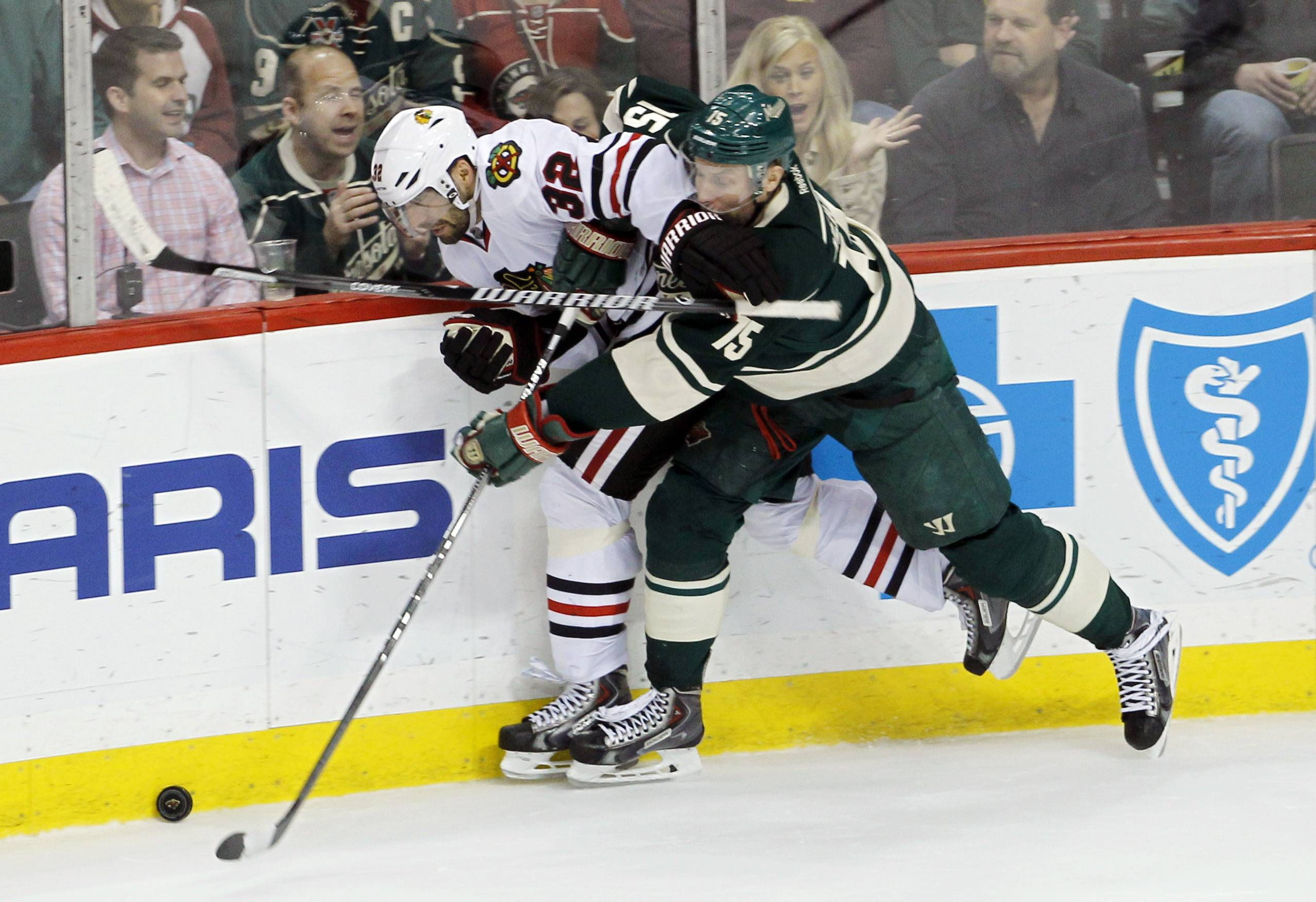 Chicago Blackhawks defenseman Michal Rozsival (32) and Minnesota Wild left wing Dany Heatley (15) battle for the puck during the third period.