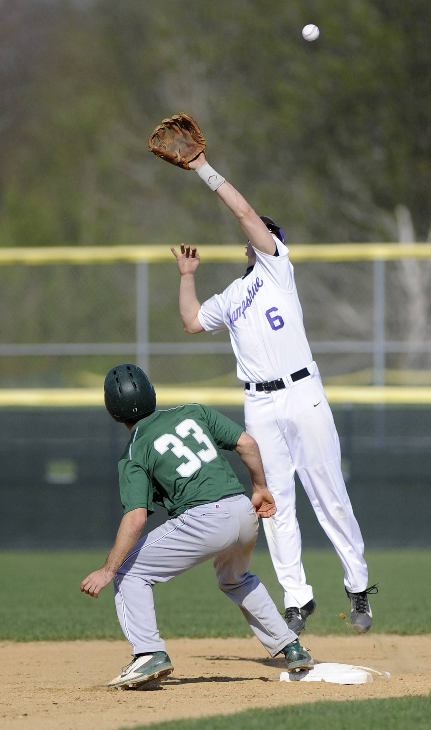 Grayslake Central's Jay Hoffmann watches as the ball flies over the mitt of Hampshire's Dillon Kuhn, and takes off for second base in the first inning at Hampshire Friday.