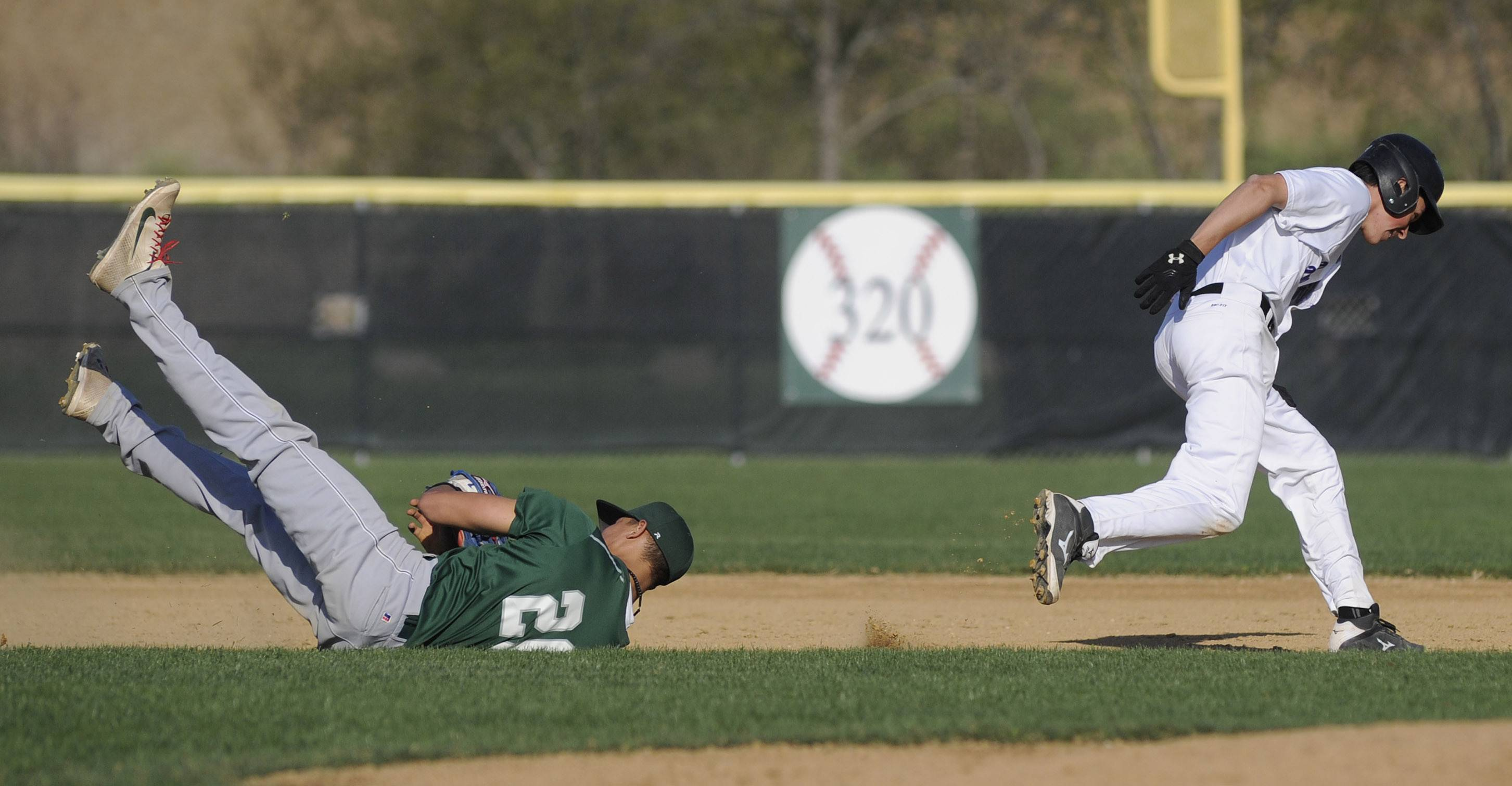 Grayslake Central's Freddie Landers tumbles to the ground after tagging out Hampshire's Alex Bahnick after chasing him between first and second base at Hampshire Friday.
