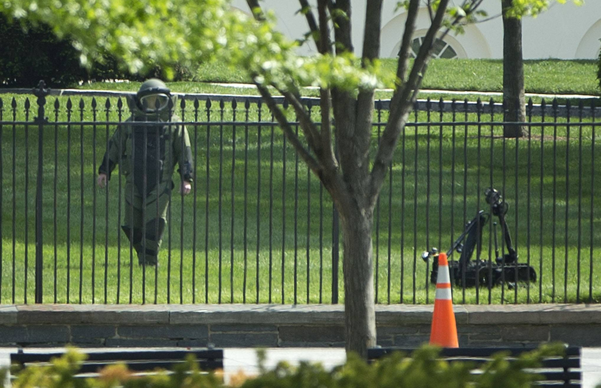 A bomb technician works with an explosives ordinance disposal robot to help recover an unknown item that was thrown over the fence Thursday on the north side of the White House in Washington. For the second time in three days, the White House was on lockdown because of a security breach. The Secret Service says two people threw something over the fence surrounding the White House complex — one person from the south side and one from the north. The two people were detained and questioned.