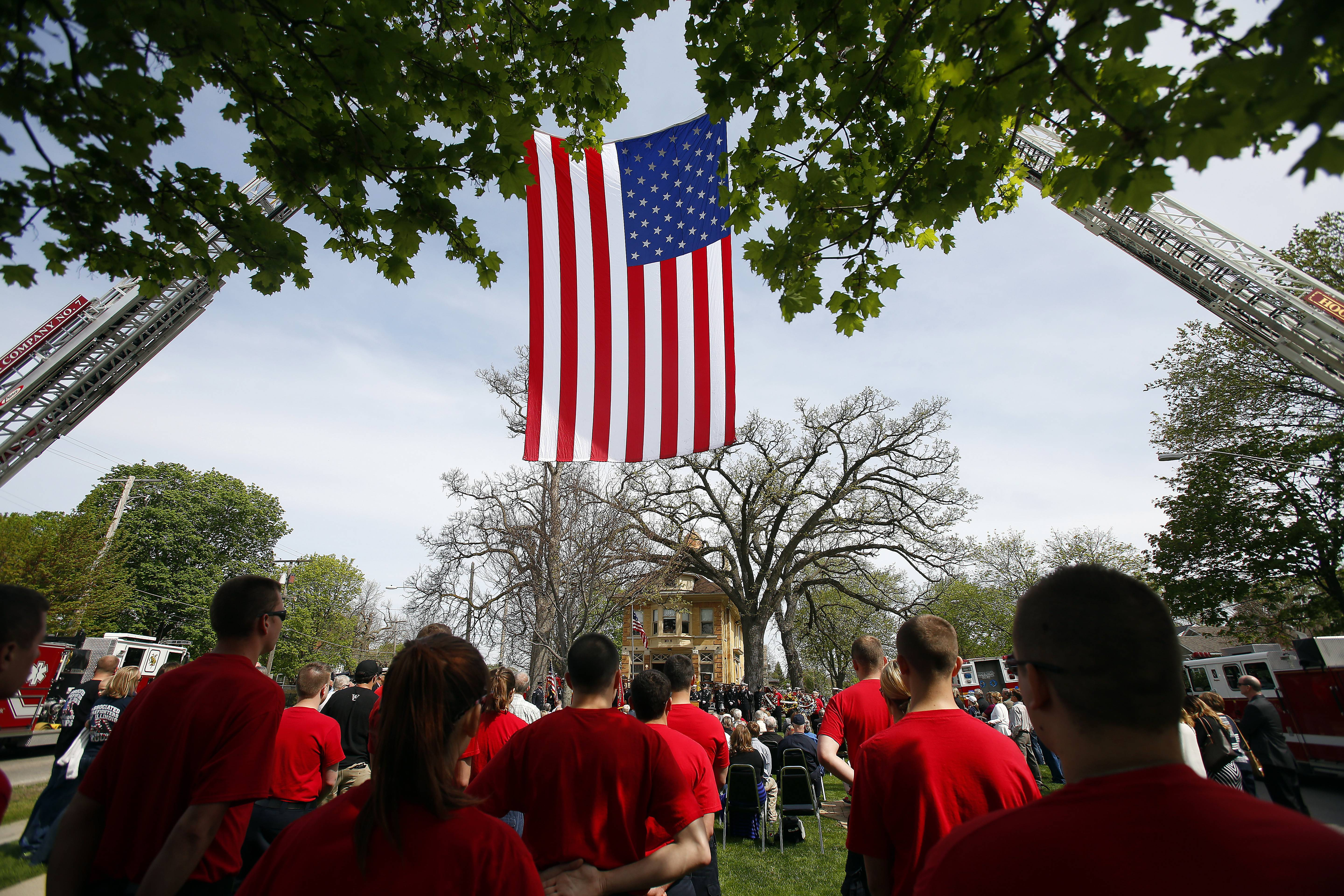 A giant American flag is held aloft over the crowd by two ladder trucks during the annual Elgin Area Firefighters Memorial Service Saturday at George Van De Voorde Firefighter Memorial Park and Elgin Fire Barn No. 5 Museum.