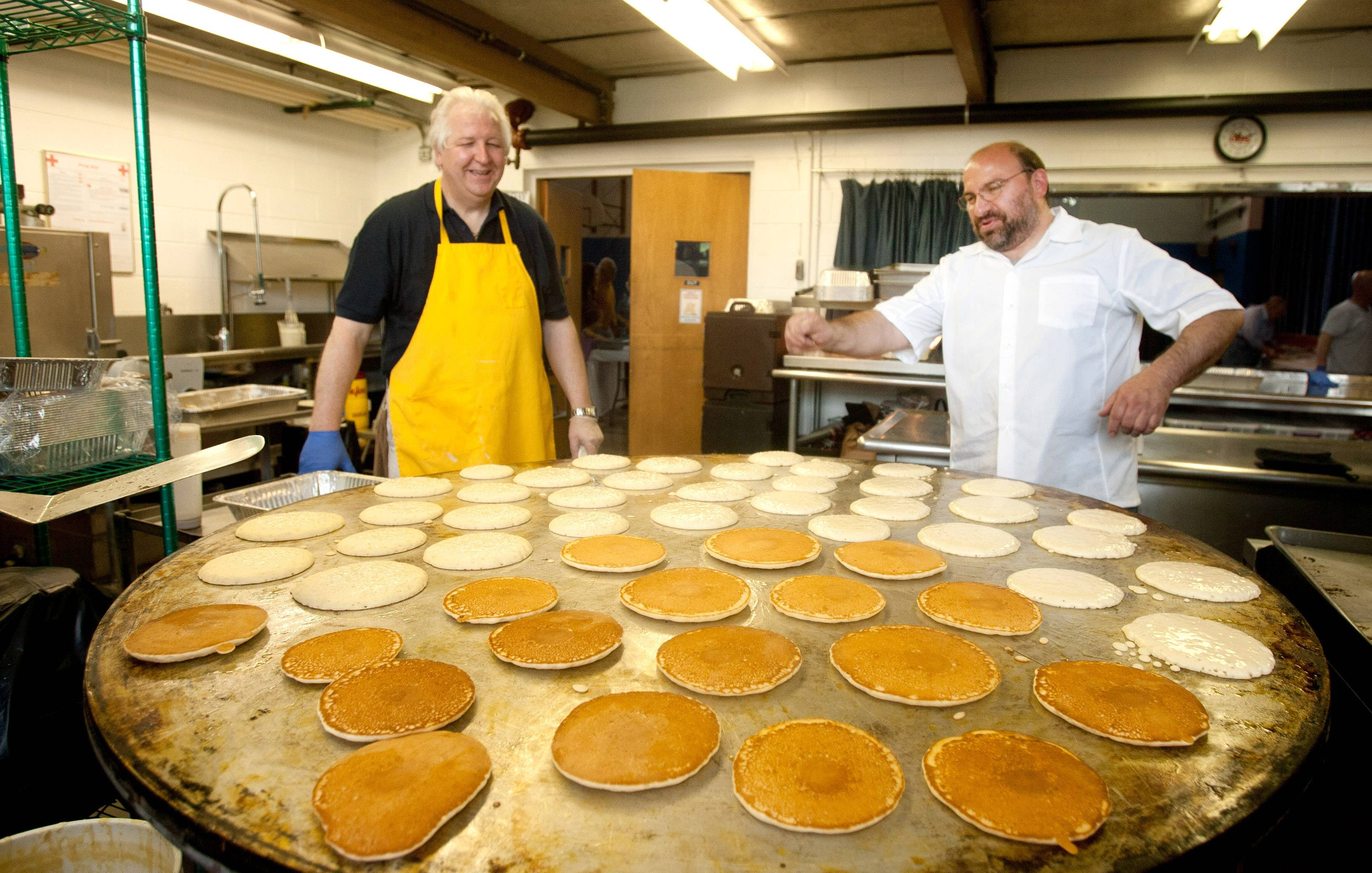Bob Olender, left, and Bob Conidi, right, chairman of the Itasca Lions Club pancake breakfast, watch a rotating hot griddle cook 48 pancakes at a time during the pancake breakfast in the Saint Luke School gymnasium in Itasca.