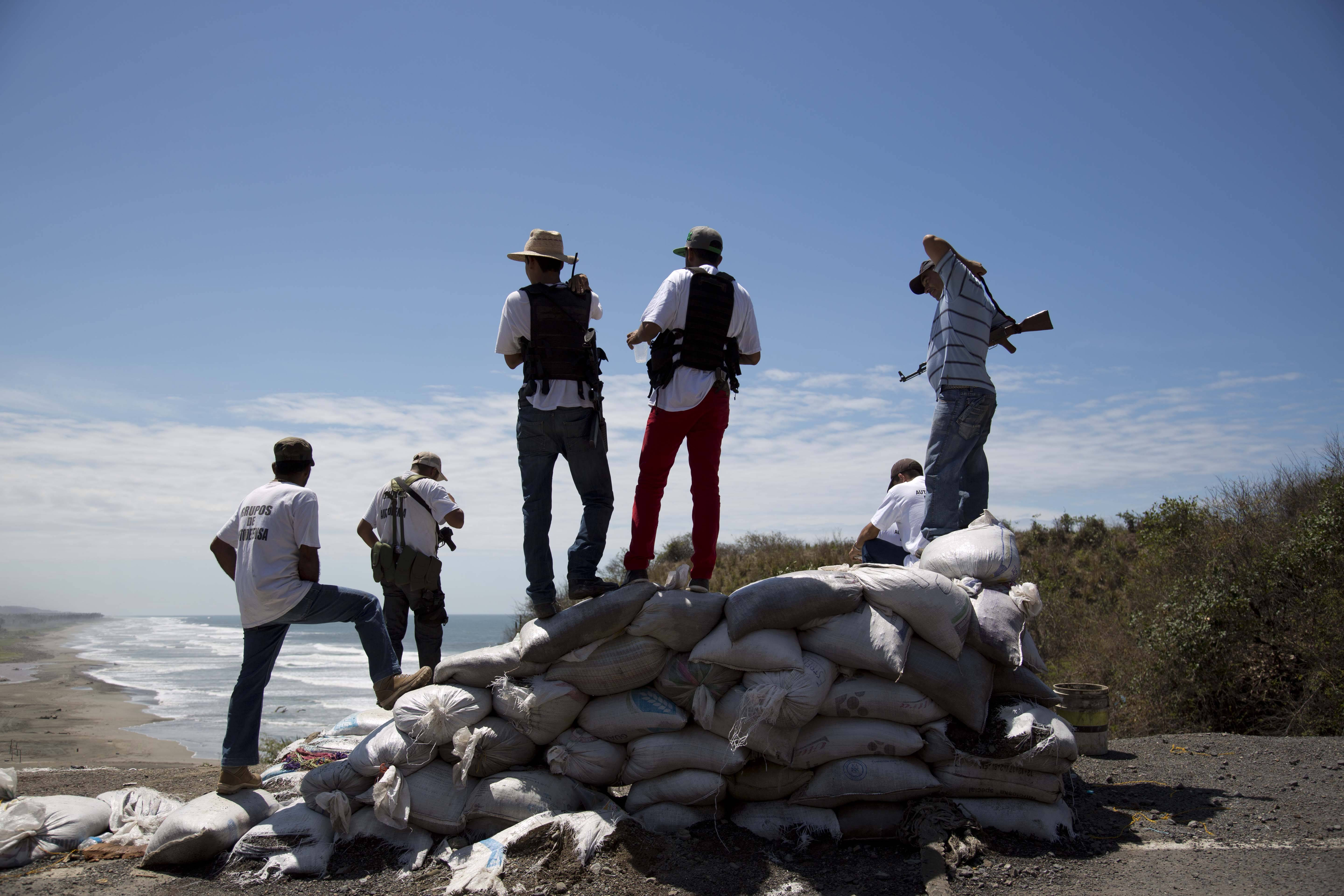 Armed men belonging to the Self-Defense Council of Michoacan look out toward the sea as they guard a checkpoint set up by the self-defense group in Chuquiapan on the outskirts of the seaport of Lazaro Cardenas in western Mexico, Friday, May 9. Mexico's government plans on Saturday to begin demobilizing the vigilante movement that largely expelled the Knights Templar cartel when state and local authorities couldn't. But tension remained on Friday in the coastal part of the state outside the port of Lazaro Cardenas, where some self-defense groups plan to continue as they are, defending their territory without registering their arms.