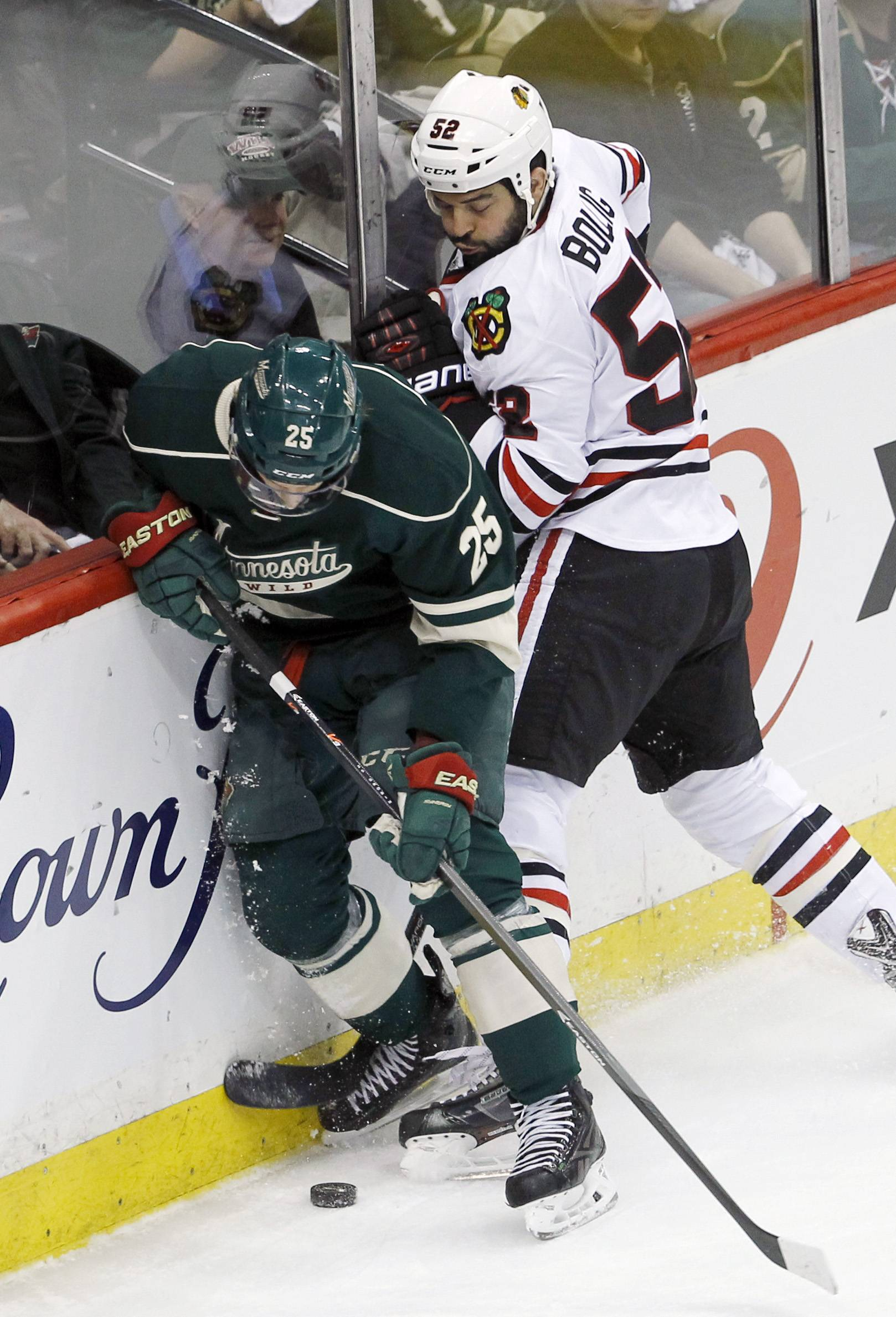 The Hawks' Brandon Bollig, here battling for the puck with the Wild's Jonas Brodin in Game 3 of the second-round Western Conference playoff series, will sit the next two games after being suspended for boarding Keith Ballard from behind in Friday's Game 4.
