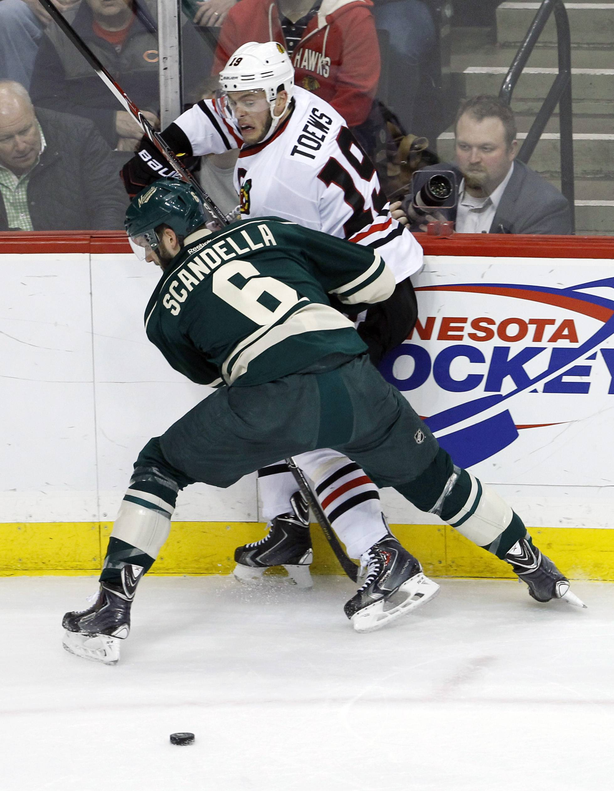 "Minnesota Wild defenseman Marco Scandella (6) pins Chicago Blackhawks center Jonathan Toews (19) against the boards and away from the puck during the first period of Game 3 of an NHL hockey second-round playoff series Tuesday in St. Paul, Minn. Toews said the team just has to put the two-game loss behind them. ""It's playoff hockey — it's not supposed to be easy,"" Toews said."