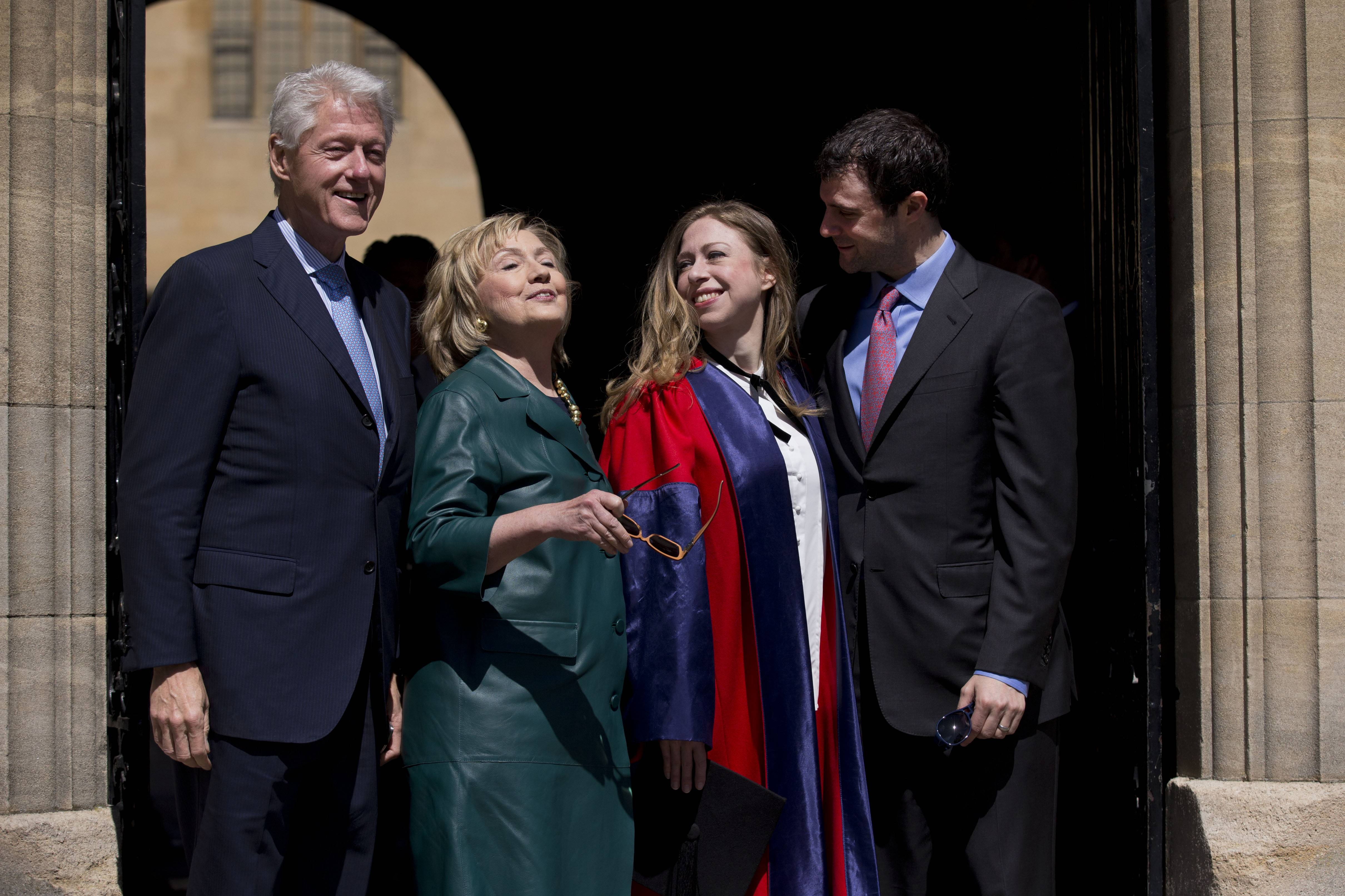 Former U.S. Secretary of State Hillary Rodham Clinton, second left, takes off her sunglasses Saturday to pose for a group photograph with her husband former President Bill Clinton, left, their daughter Chelsea, second right, and her husband Marc Mezvinsky, as they leave after attending Chelsea's Oxford University graduation ceremony at the Sheldonian Theatre in Oxford, England.